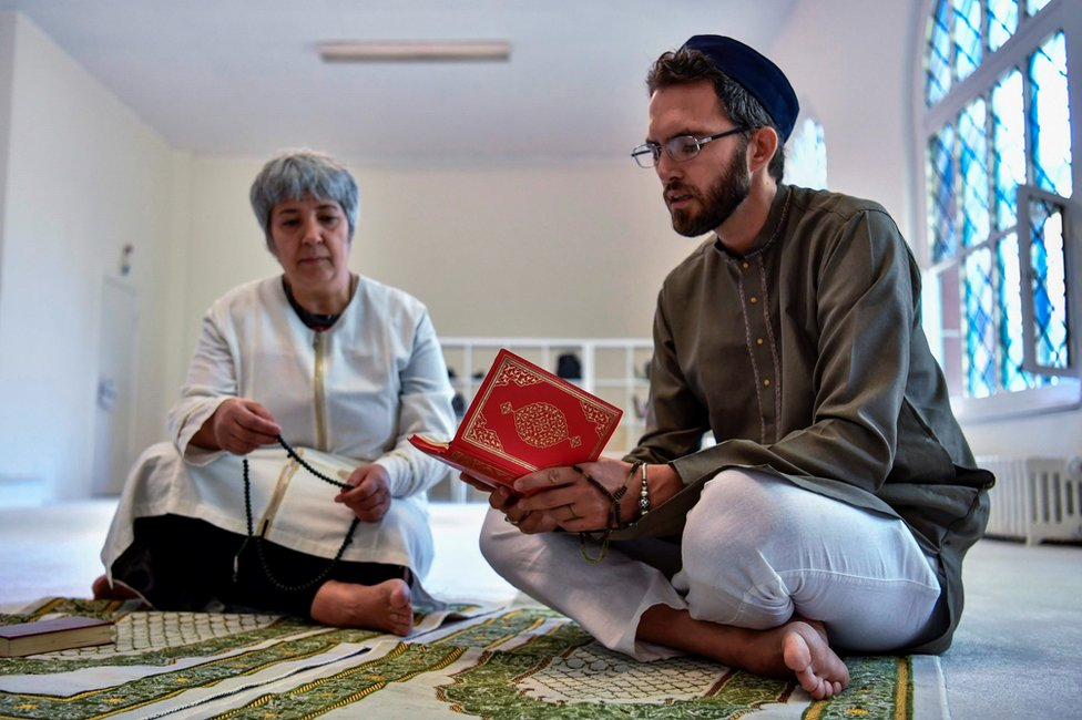 Seyran Ates listens as openly gay French imam Ludovic-Mohamed Zahed reads verses of the Koran