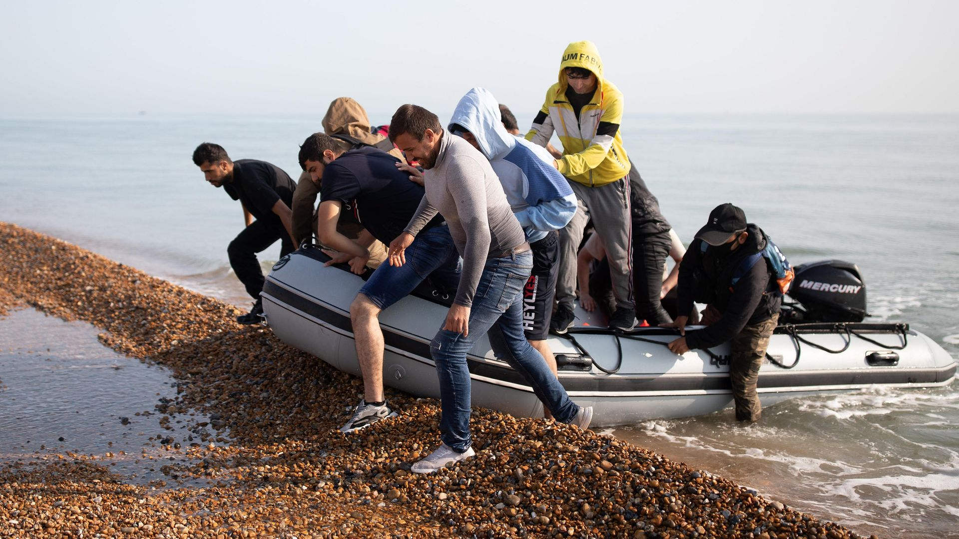 Migrants land on Deal beach last month after crossing the English channel from France in a dinghy - Credit: Getty Images