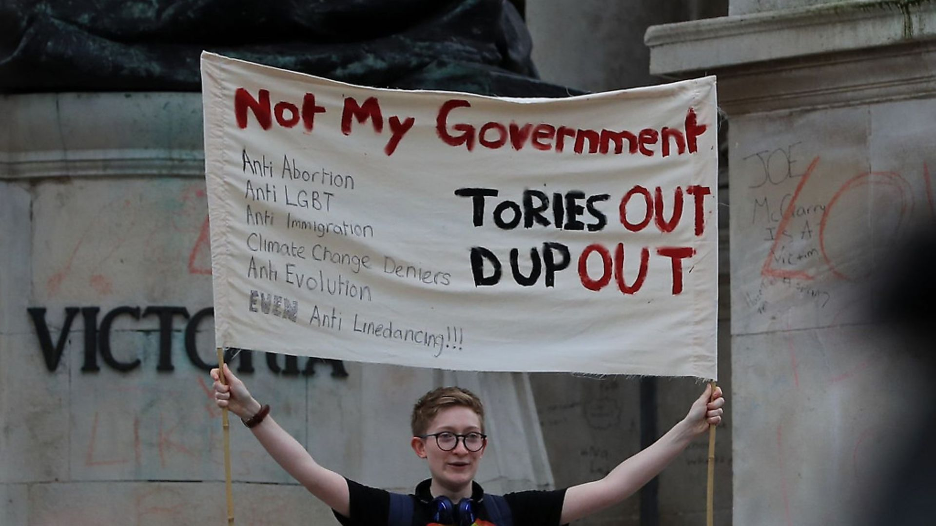 A protester holds up a sign at a demonstration in Liverpool - Credit: PA Wire/PA Images