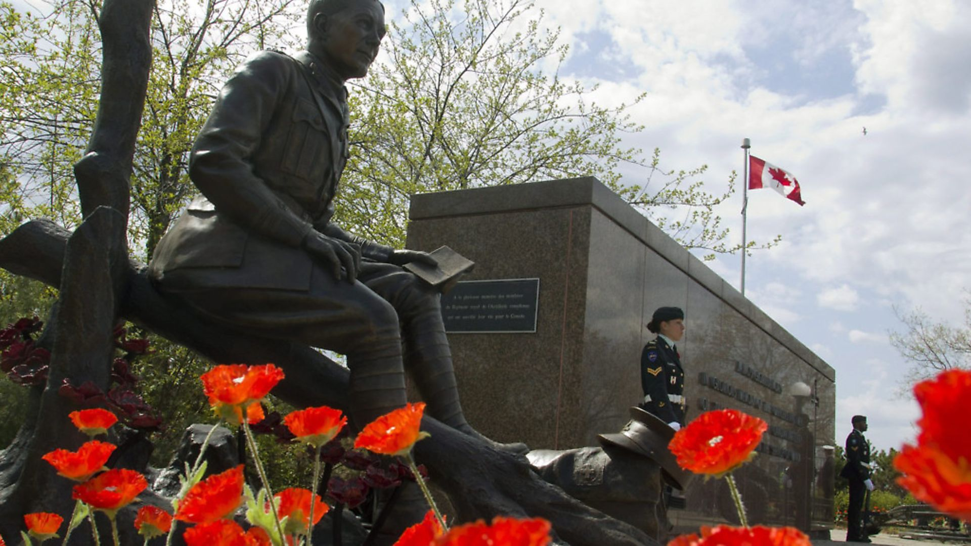 Poppies surround the newly unveiled statue of Lt.-Col. John McCrae to commemorate the Second Battle of Ypres - Credit: The Canadian Press/PA Images