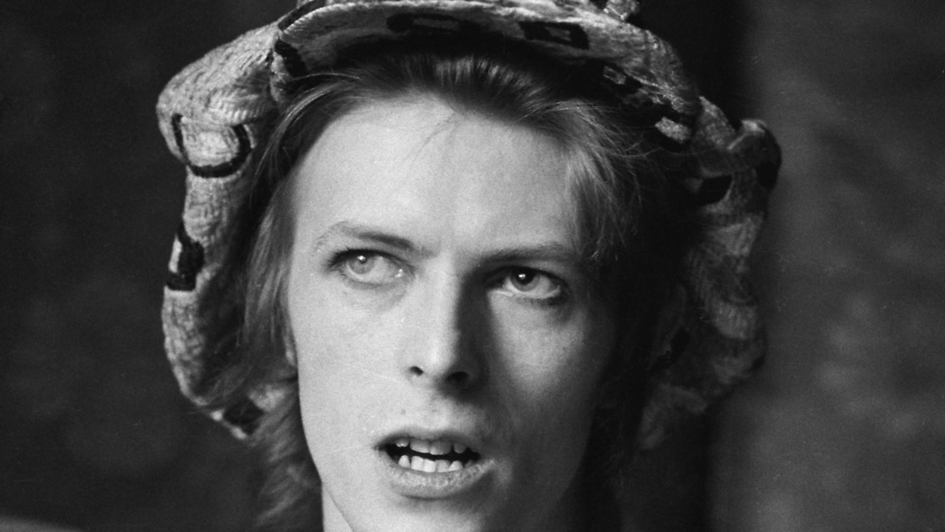 Singer David Bowie (1947 - 2016) being interviewed at his ground floor flat at Haddon Hall, where he has been redecorating the ceiling in silver paint, Beckenham, London, 24th April 1972. (Photo by Michael Putland/Getty Images) - Credit: Getty Images