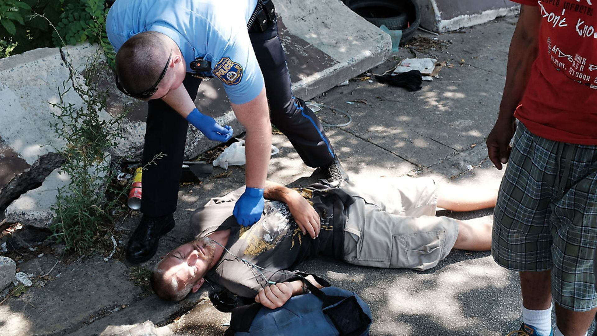A police officer in Philadelphia tries to revive a man who has overdosed. Photo: Spencer Platt/Getty Images - Credit: Getty Images