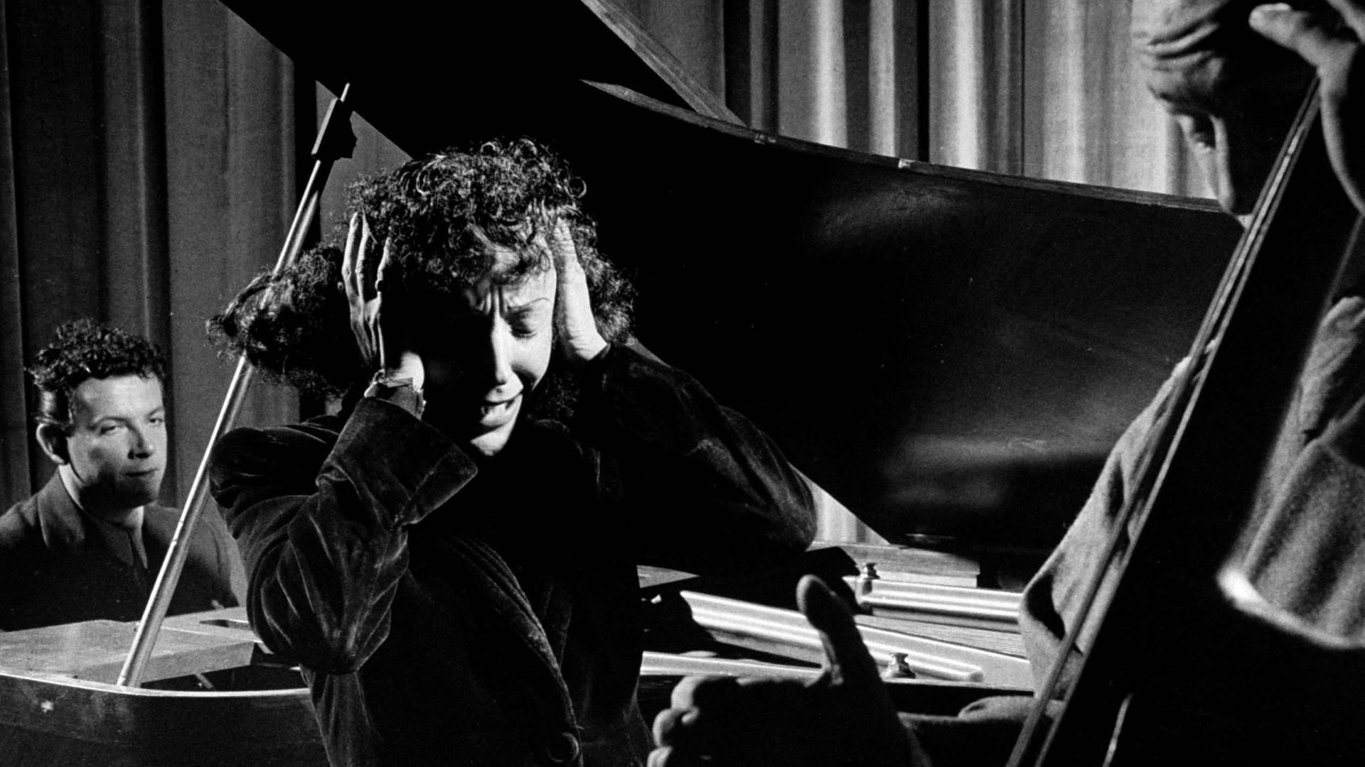 Edith Piaf holding her hands to her head while performing - Credit: The LIFE Picture Collection via
