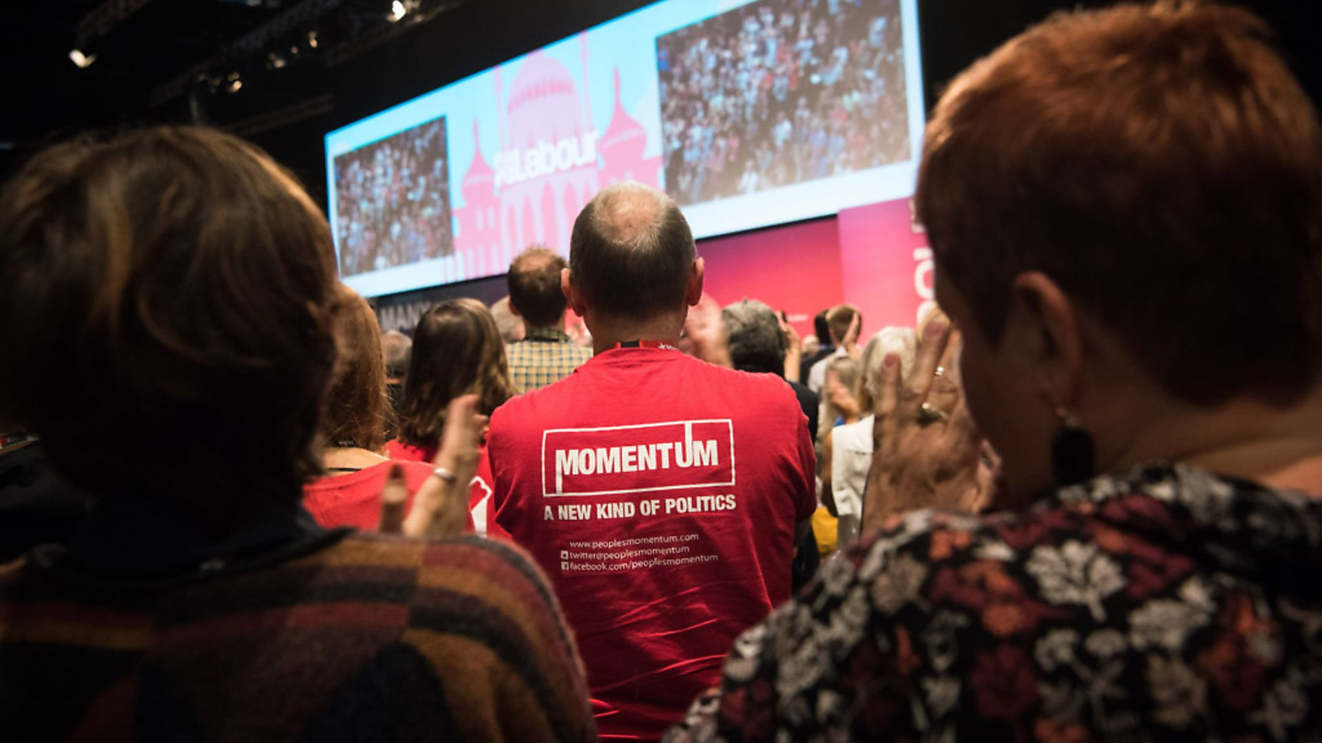 A Momentum supporter watches as Jeremy Corbyn gives his Leader's Speech. Photo: Matt Crossick/EMPICS Entertainment. - Credit: Empics Entertainment