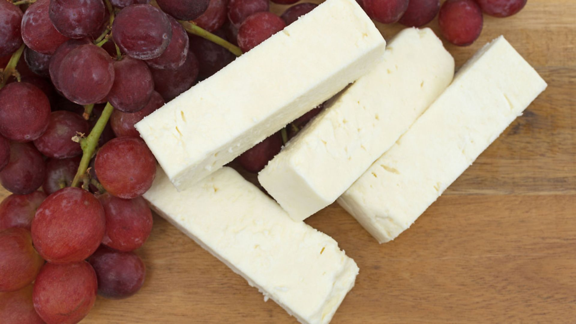 A generic photo of Close view of several large slices of feta cheese on a wood cheese board with a bunch of fresh red grapes. See PA Feature CHRISTMAS Food Swaps. Picture credit should read: PA Photo/thinkstockphotos. WARNING: This picture must only be used to accompany PA Feature CHRISTMAS Food Swaps - Credit: Archant