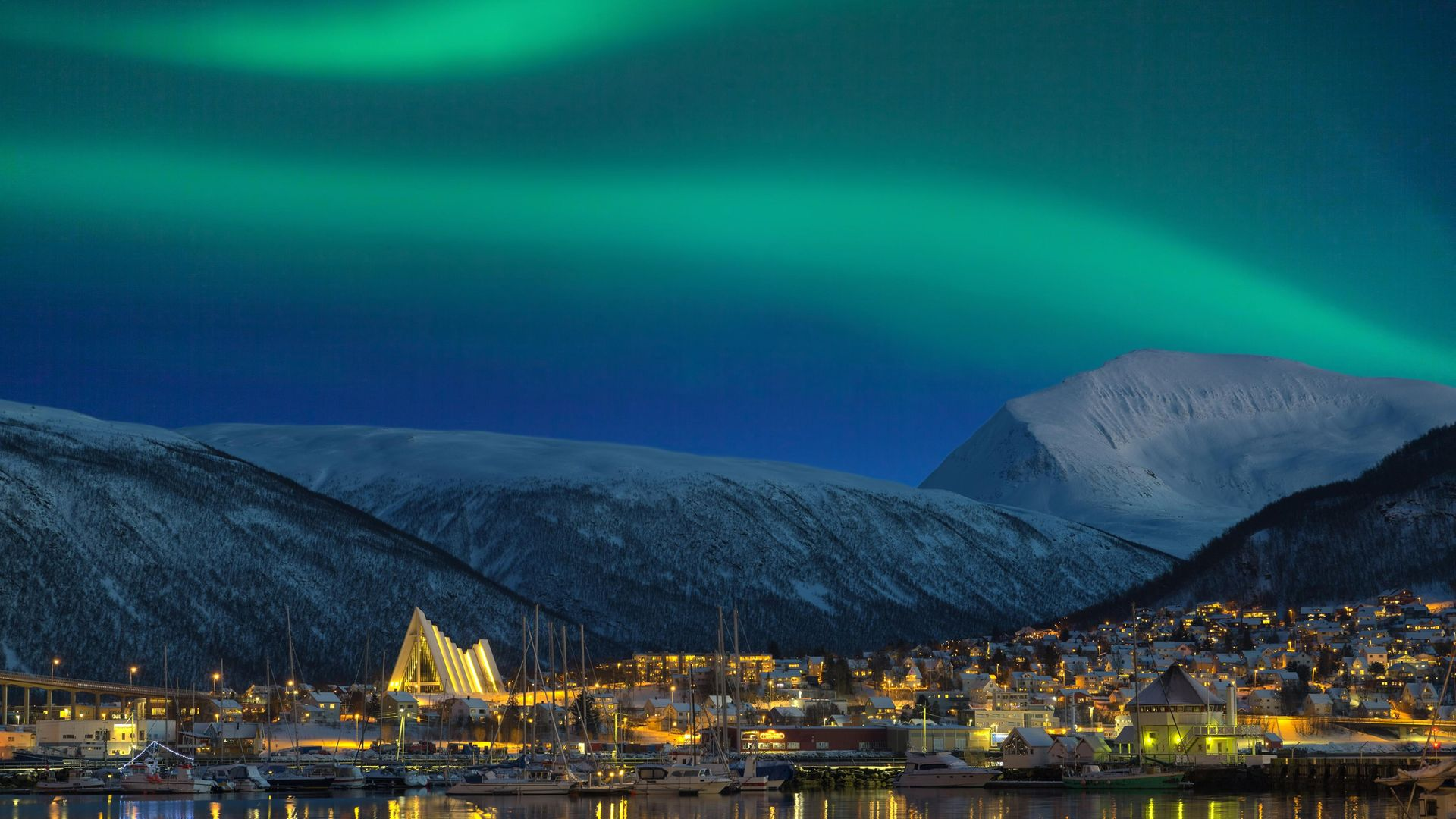 The view at night on illuminated Tromso city with cathedral and majestic aurora borealis - Credit: Getty Images