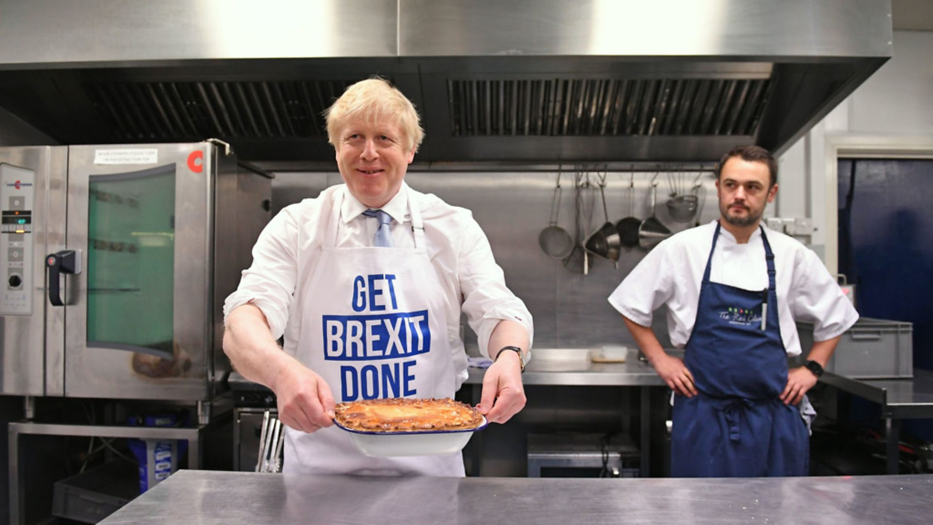 Prime Minister Boris Johnson holds a freshly baked pie while wearing a 'get Brexit done' apron. - Credit: Stefan Rousseau/PA.