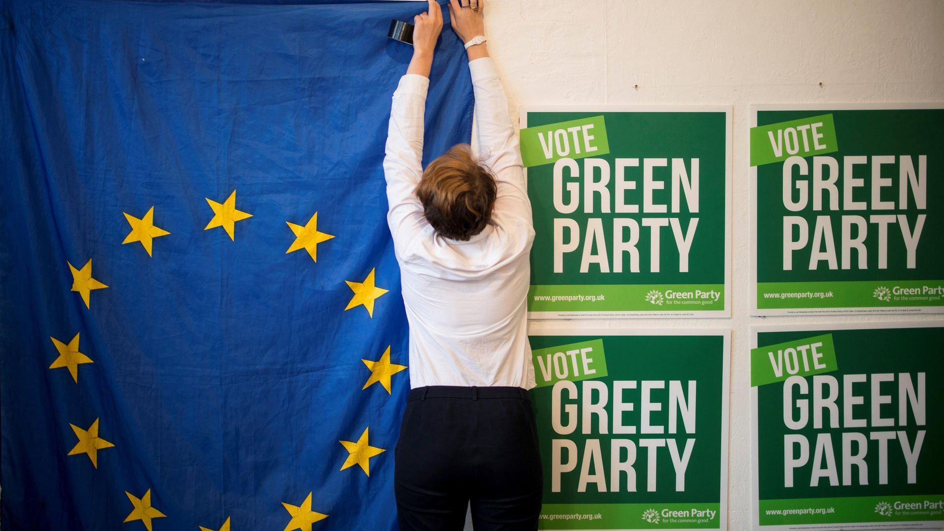 Volunteers hang a EU flag as they prepare the room for the launch of the Green Party's European election campaign in central London on May 8, 2019 - Credit: AFP via Getty Images