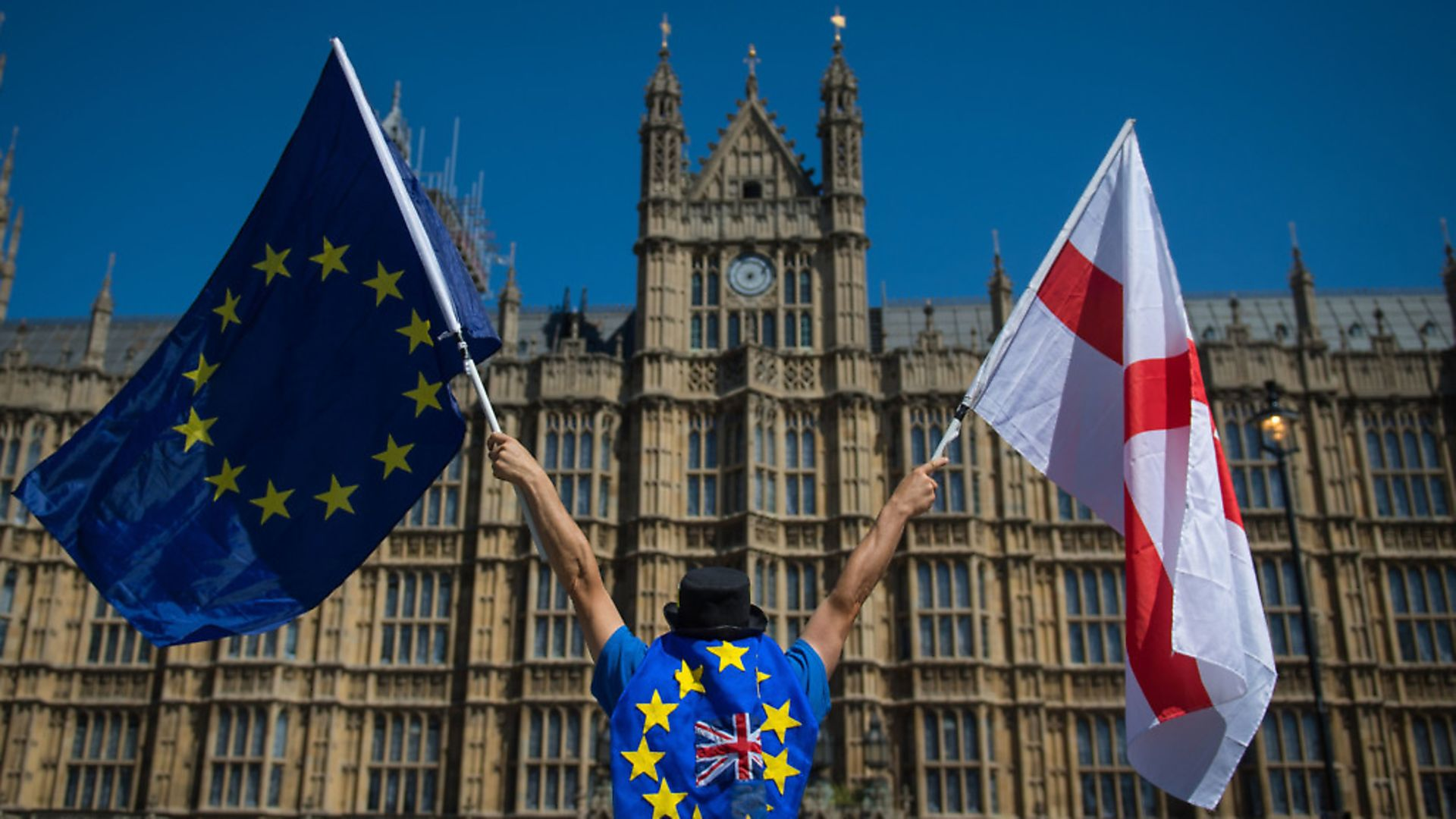 An anti-Brexit demonstrator holding the European Union and England flags outside the Houses of Parliament. Photograph: Dominic Lipinski. - Credit: PA Wire/PA Images