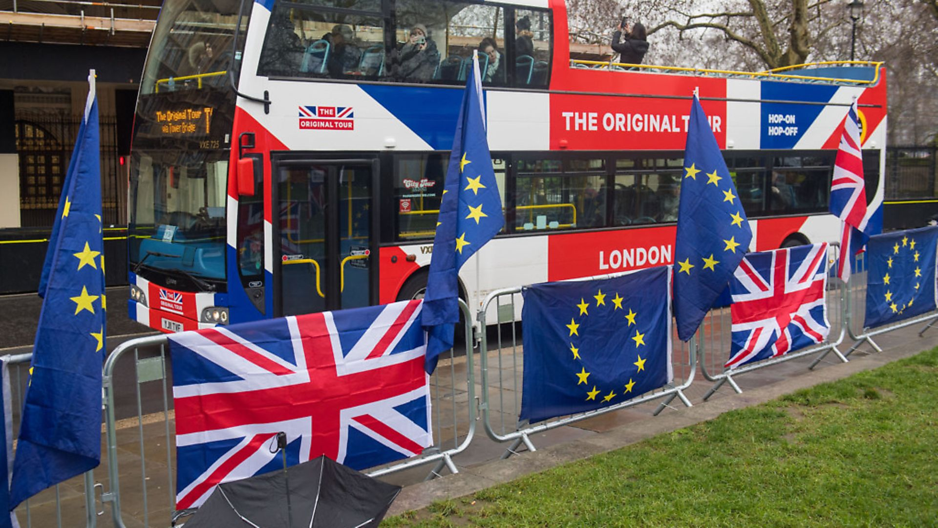 A tour bus passes anti-Brexit banners outside the Houses of Parliament. Photograph: Dominic Lipinski/PA. - Credit: PA Wire/PA Images