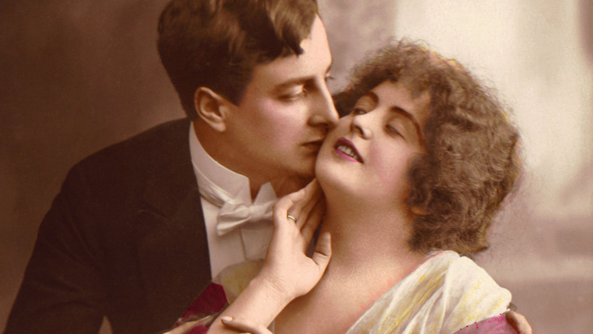 Hand tinted photograph shows a man in evening dress kisses a woman's cheek and embraces her, early 20th Century. (Photo by Stock Montage/Getty Images) - Credit: Getty Images