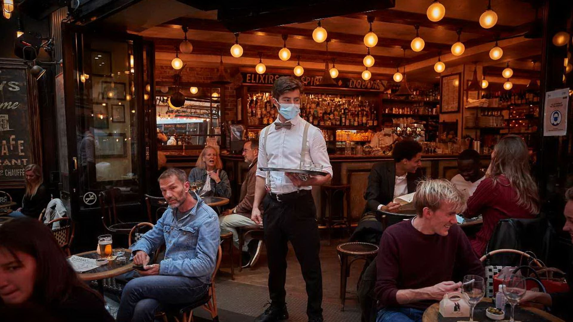 A waiter serving drinkers during the pandemic in Paris - Credit: Kiran Ridley/Getty Images