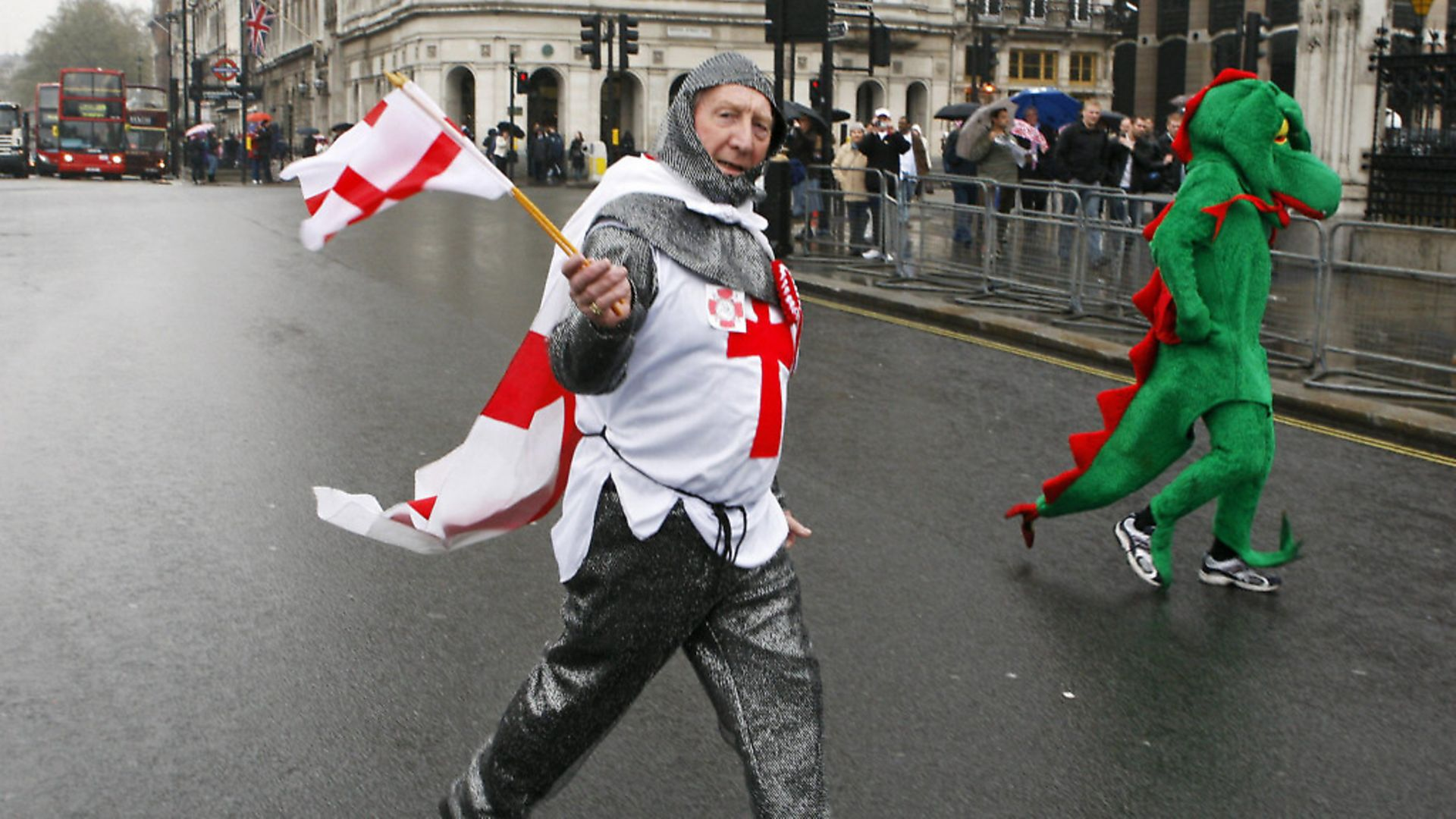 A man dressed as Saint George crosses the road beside a man dressed as a dragon outside the Houses of Parliament as part of a political protest by The English Democrats. (ADRIAN DENNIS/AFP/Getty Images) - Credit: AFP/Getty Images
