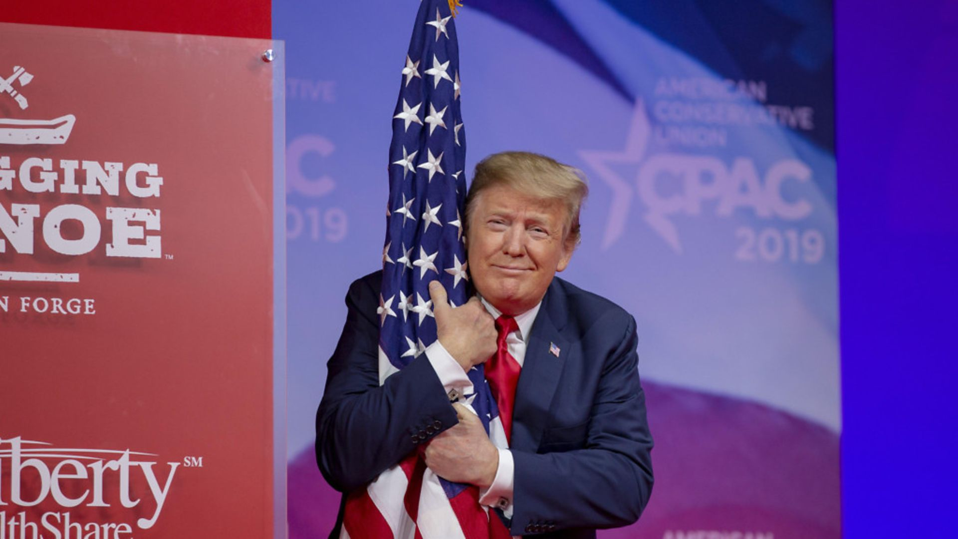 U.S. President Donald Trump hugs the U.S. flag - Credit: Getty Images