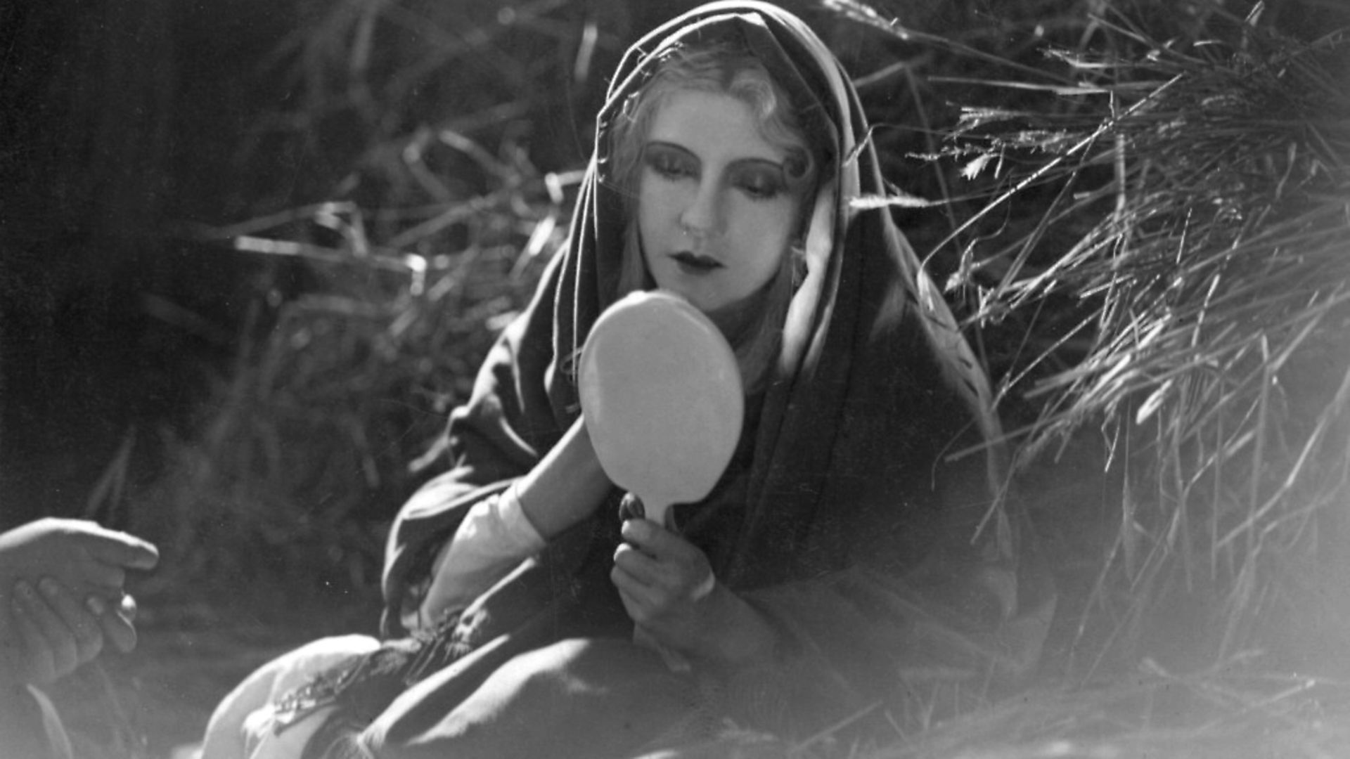 Brigitte Helm studies herself in the German silent film 'The Burning Mill'.  (Photo by Hulton Archive/Getty Images) - Credit: Getty Images