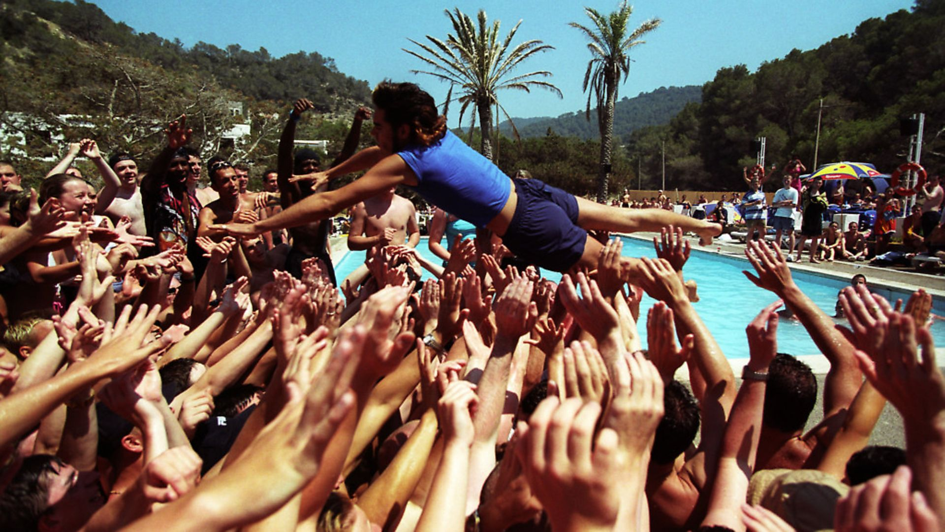 A holiday rep diving into a crowd of people, at a pool party, Club 18-30 Ibiza, 2001. (Photo by: PYMCA/Universal Images Group via Getty Images) - Credit: Universal Images Group via Getty