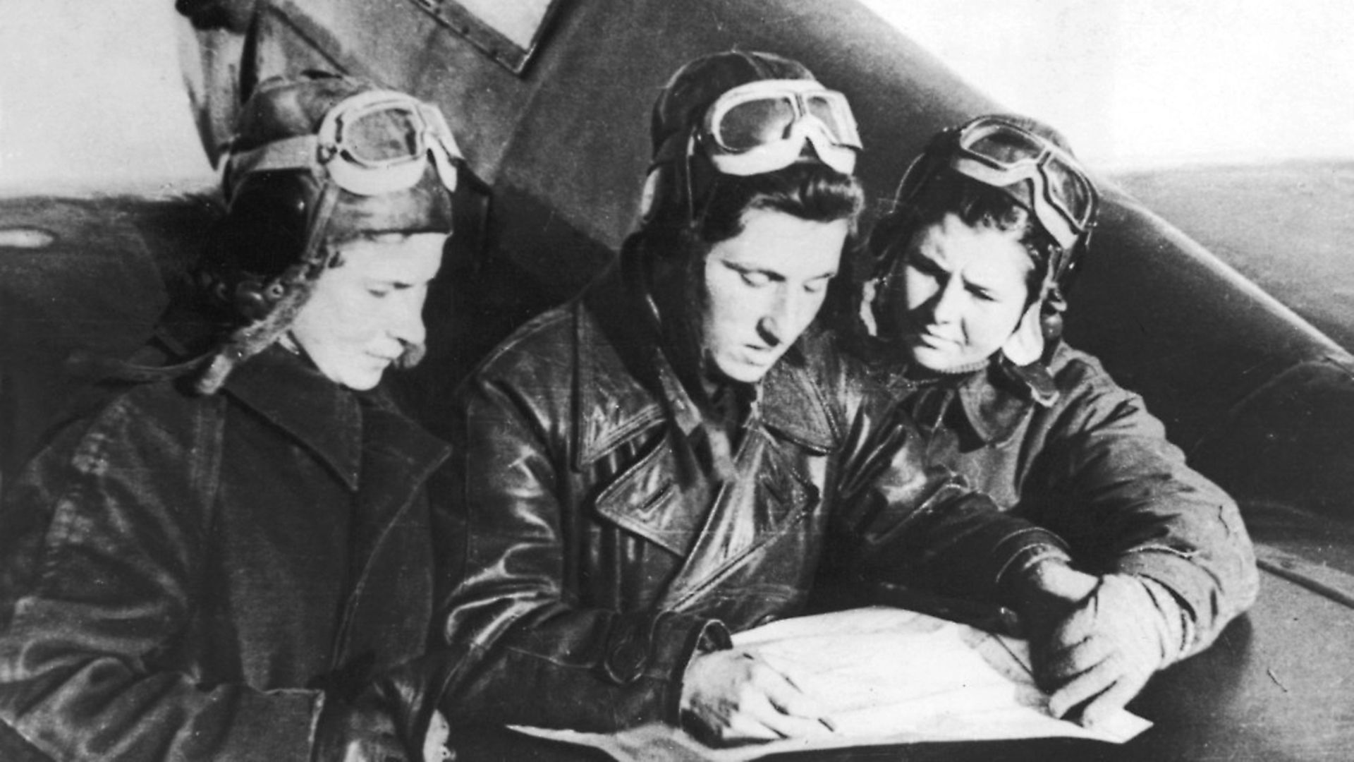 Russian female fighter pilots Lilya Litvyak (1921 - 1943) (left), Katerina Budanova (1916 - 1943) (center), and Mariya Kuznetsova, all of the 437th fighter regiment, plot their flight plans on the tailplane of a Yakovlev Yak-1 fighter plane, Russia, mid 1942. (Photo by Mansell/The LIFE Picture Collection via Getty Images/Getty Images) - Credit: The LIFE Picture Collection via