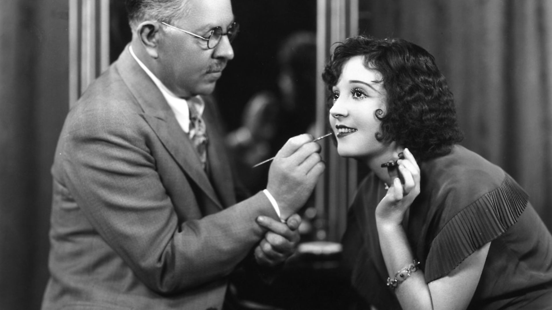 Max Factor, Polish businessman and founder of cosmetics company, Max Factor, demonstrates the technique of applying lipstick on US silent film actress Madge Bellamy. Photo: Margaret Chute/Hulton Archive/Getty Images - Credit: Getty Images