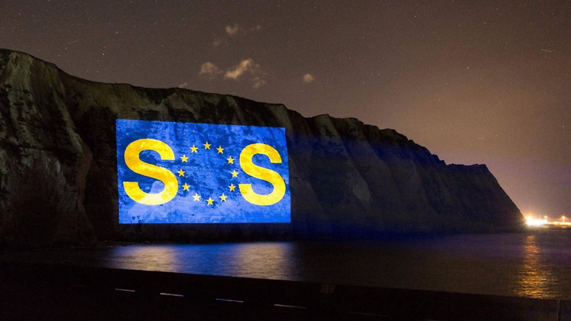 A giant SOS message is projected on to the white cliffs of Dover. Photograph: Led By Donkeys. - Credit: Archant