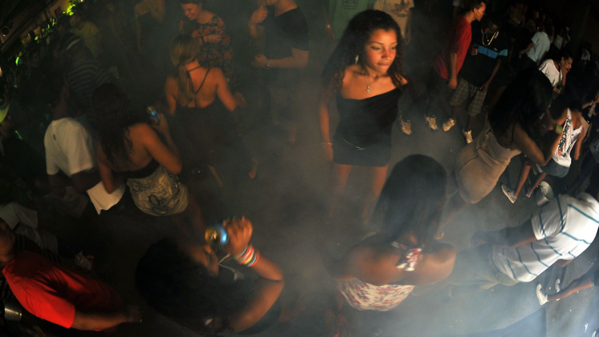 """Brazilian youngsters enjoy a """"Baile Funk"""" party at the Rocinha shantytown, in Rio de Janeiro, on March 25, 2012. In the last year, funk parties have been losing ground due to the police occupation in the favelas. AFP PHOTO / Christophe Simon (Photo credit should read CHRISTOPHE SIMON/AFP/Getty Images) - Credit: AFP/Getty Images"""