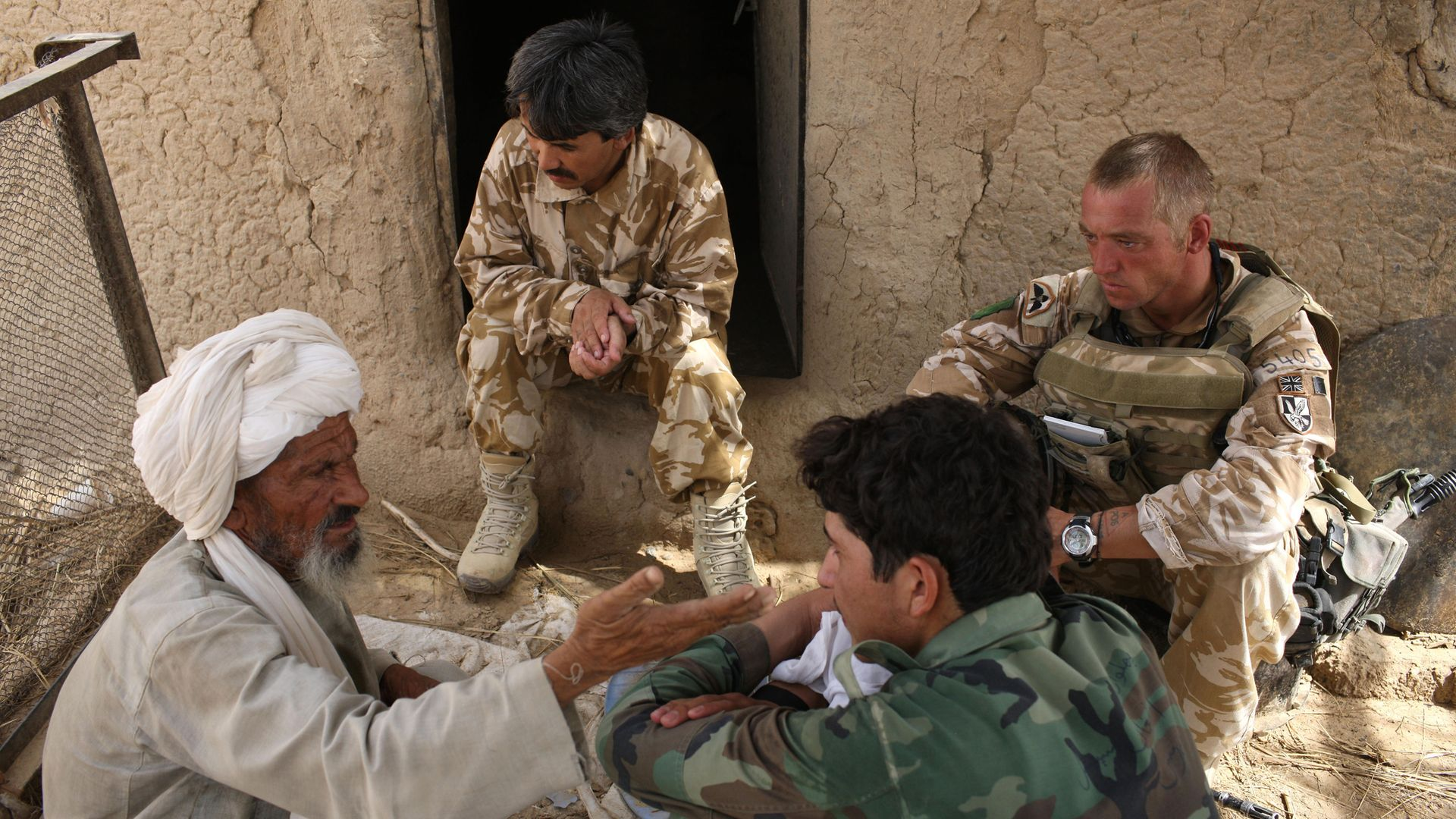A British solider and his interpreters question an Afghan in Kandahar in 2008 - Credit: Getty Images