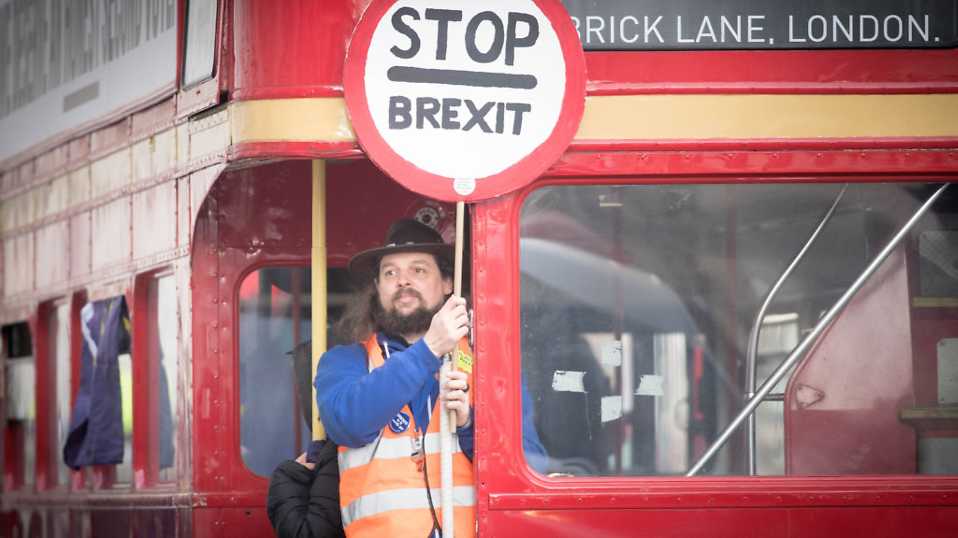A man holds a 'Stop Brexit' sign aboard a campaign bus travelling down Whitehall. Photograph: Stefan Rousseau/PA. - Credit: PA Archive/PA Images