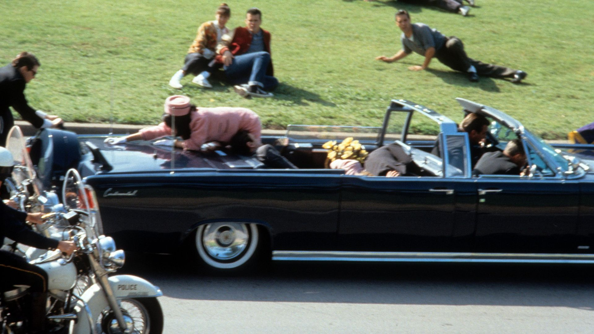 Jodie Farber reaches across the car in a scene from the film 'JFK', 1991. (Photo by Warner Brothers/Getty Images) - Credit: Getty Images