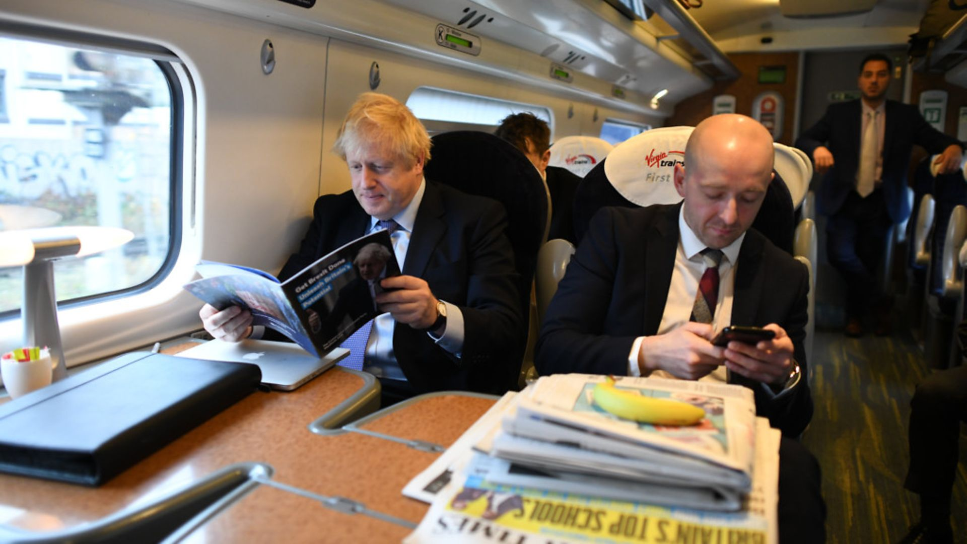 Boris Johnson, sitting with his former Director of Communications, Lee Cain (right), with a stack of newspapers on the train. - Credit: PA Wire/PA Images
