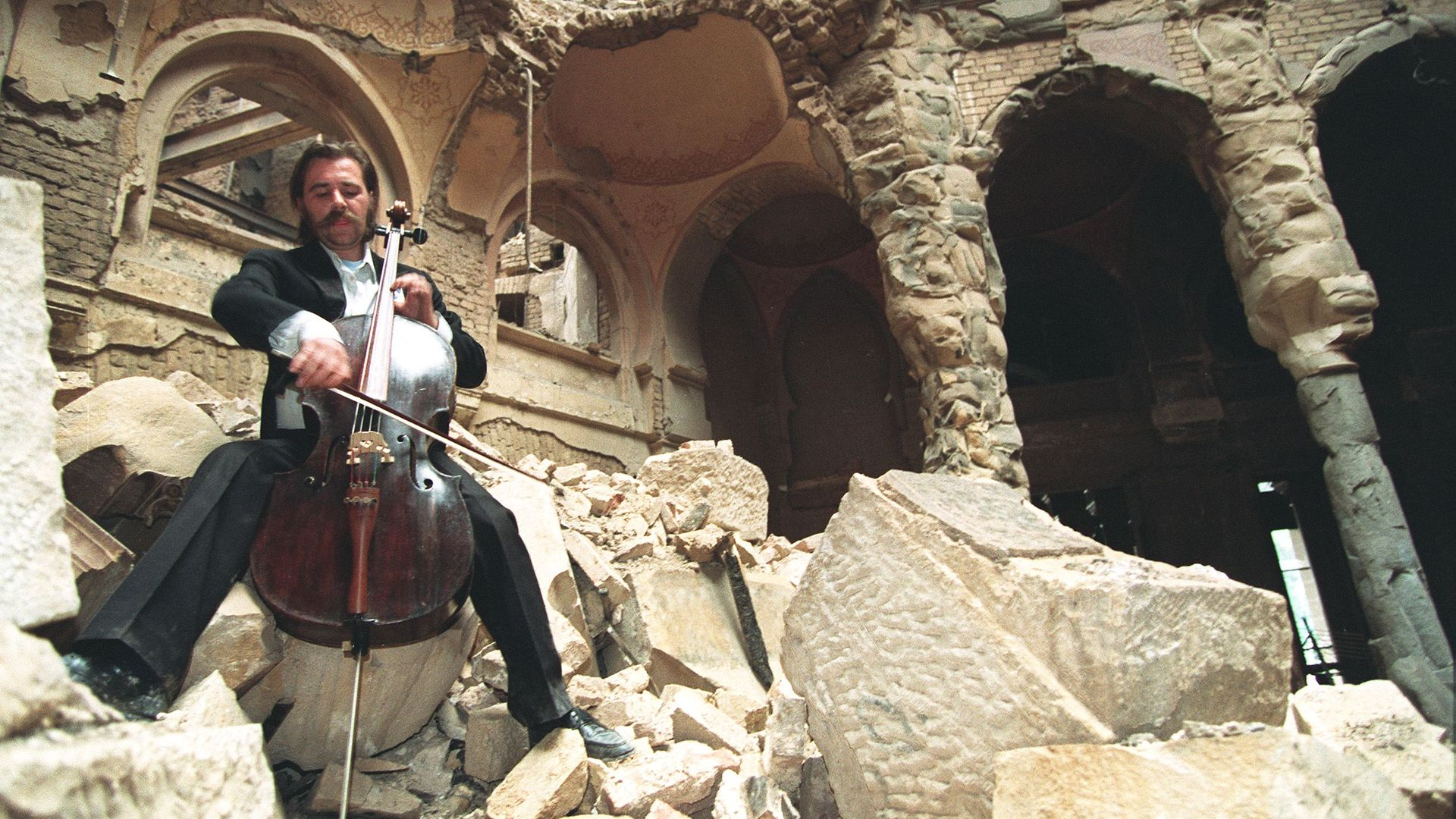 Cellist Vedran Smailovic playing Strauss in the bombed National Library in Sarajevo, in September 1992 shows. (Photo credit should read MICHAEL EVSTAFIEV/AFP via Getty Images) - Credit: AFP via Getty Images