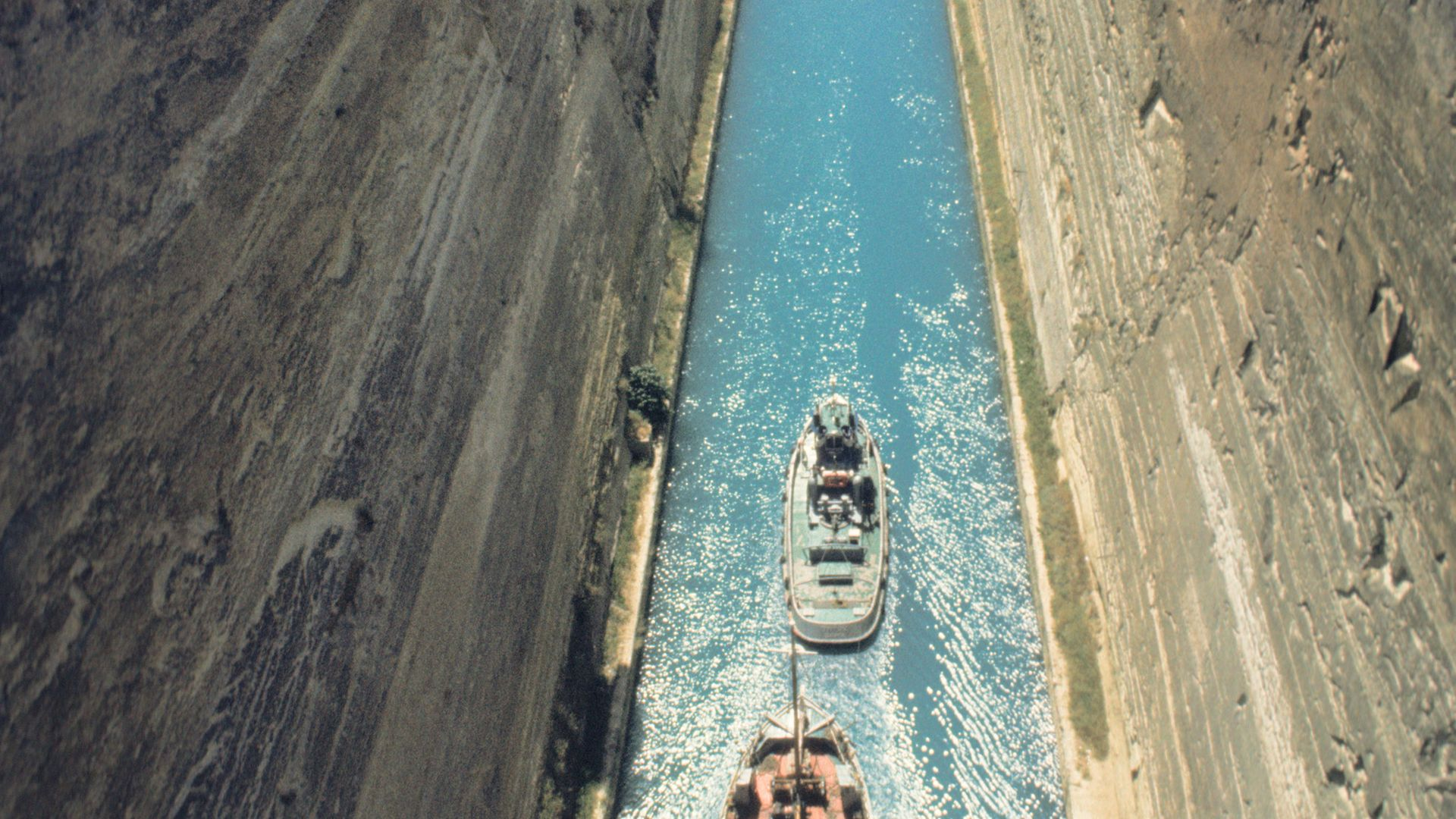 A tug boat and a larger vessel pass along the Corinth canal, in Greece - Credit: Universal Images Group via Getty