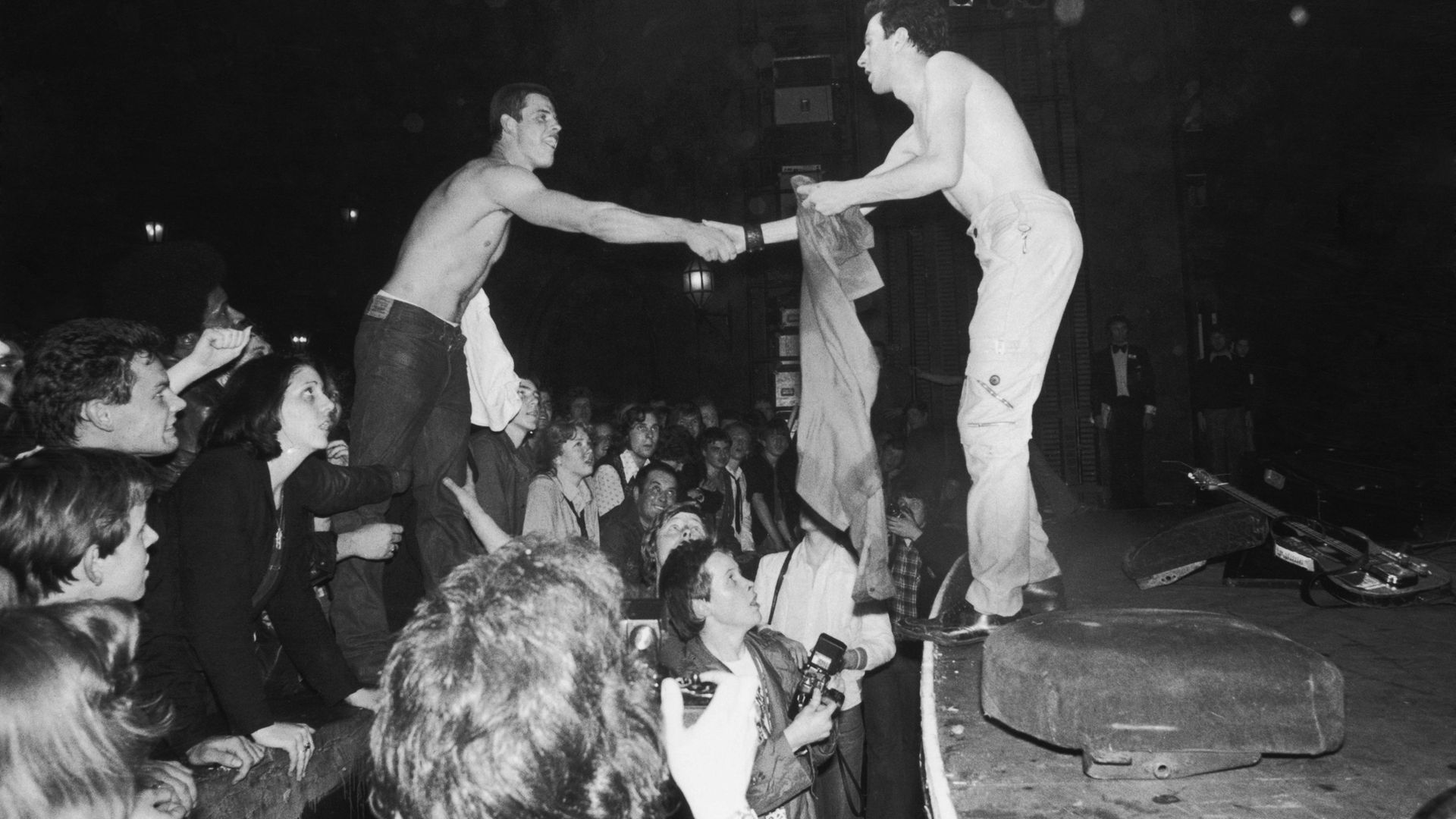 Joe Strummer (1952 - 2002), lead singer of punk rock band The Clash, exchanges shirts with a fan at The Rainbow Theatre, London - Credit: Getty Images