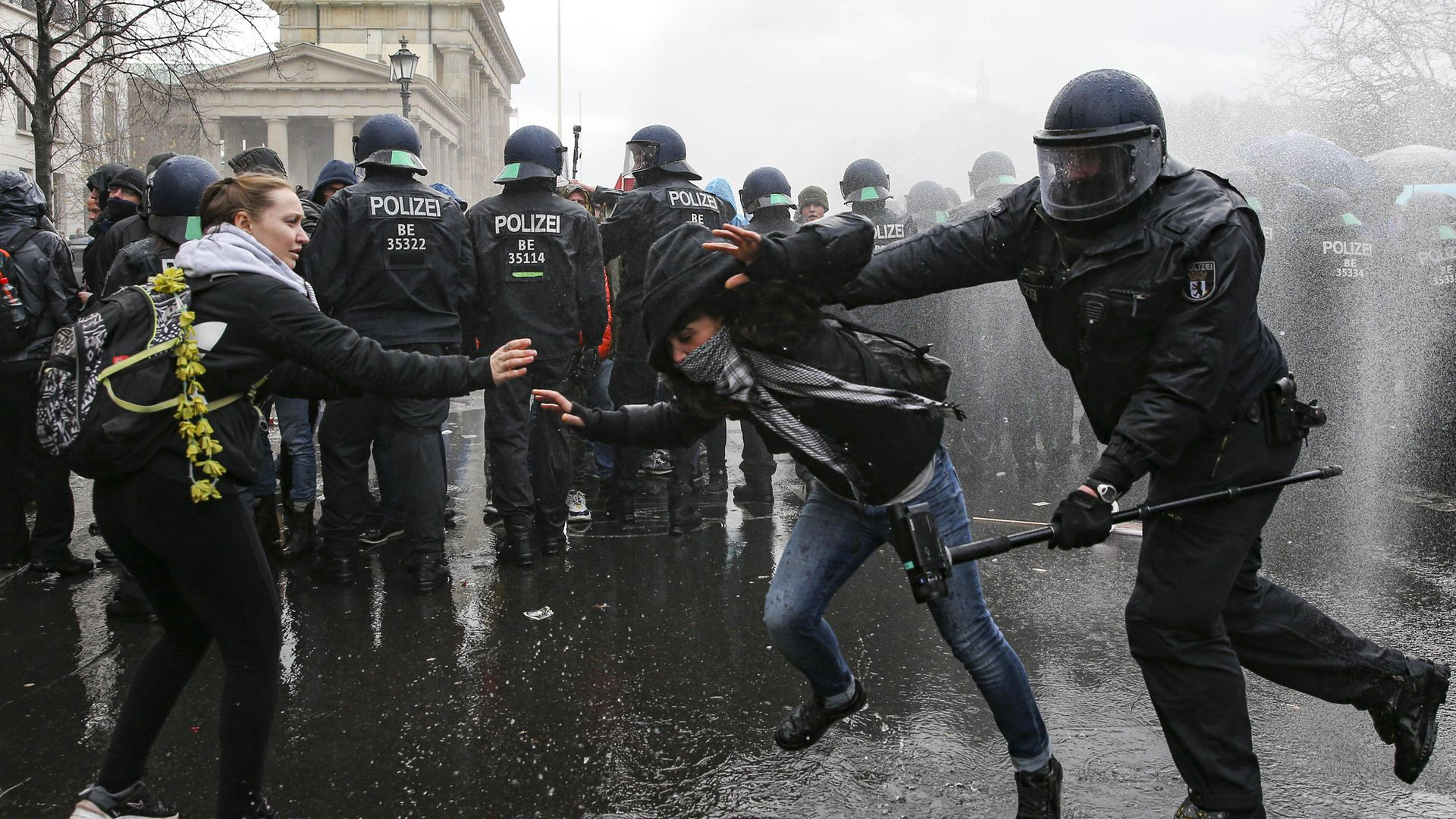 Police clash with a demonstrator near the German parliament, as water cannons are used to break up a protest against coronavirus restrictions - Credit: Anadolu Agency via Getty Images