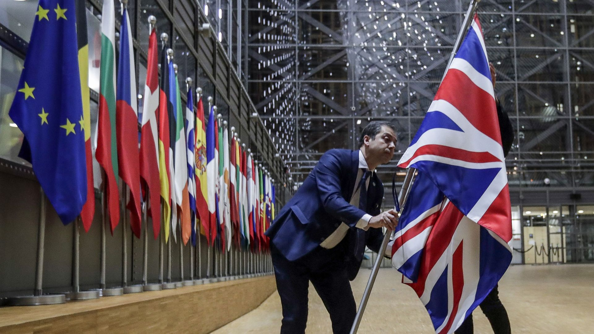 EU Council staff members remove the United Kingdom's flag from the European Council building in Brussels - Credit: POOL/AFP via Getty Images