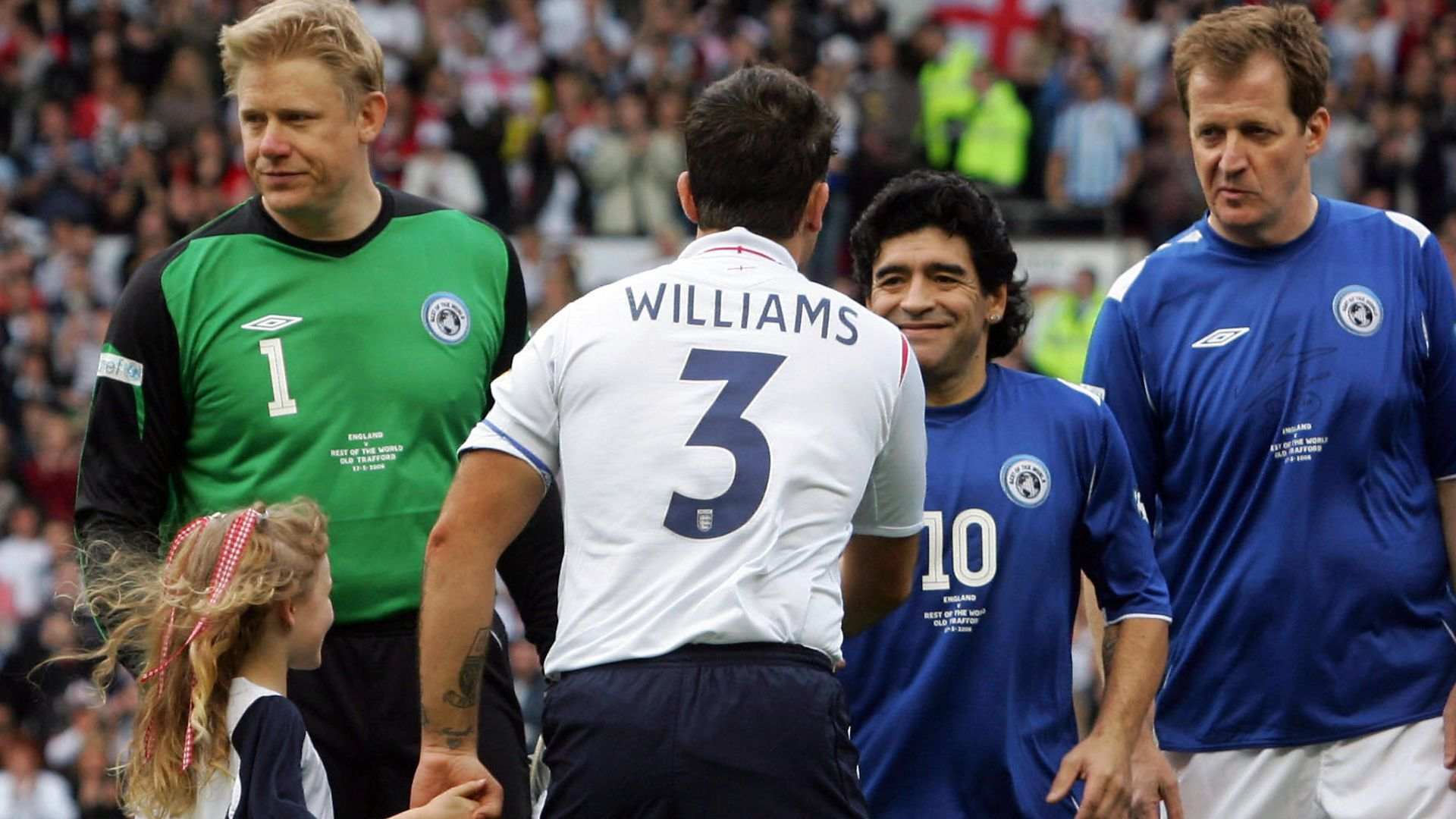 Diego Maradona, lining up alongside Alastair Campbell (r) and  Peter Schmeichel (l), greets Robbie Williams at the start of the Soccer Aid charity match at Old Trafford, in 2006 - Credit: AFP via Getty Images