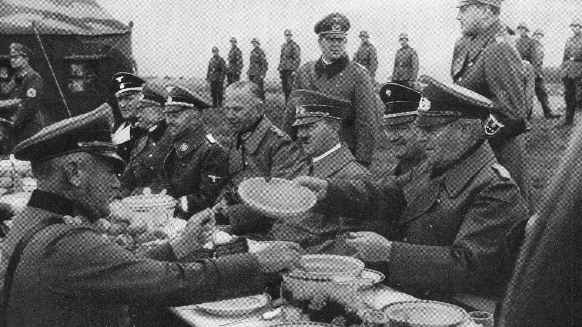 Nazi leader Adolf Hitler dines alfresco with a group of generals, circa 1940 (question one) - Credit: Henry Guttmann/Hulton Archive/Getty Images