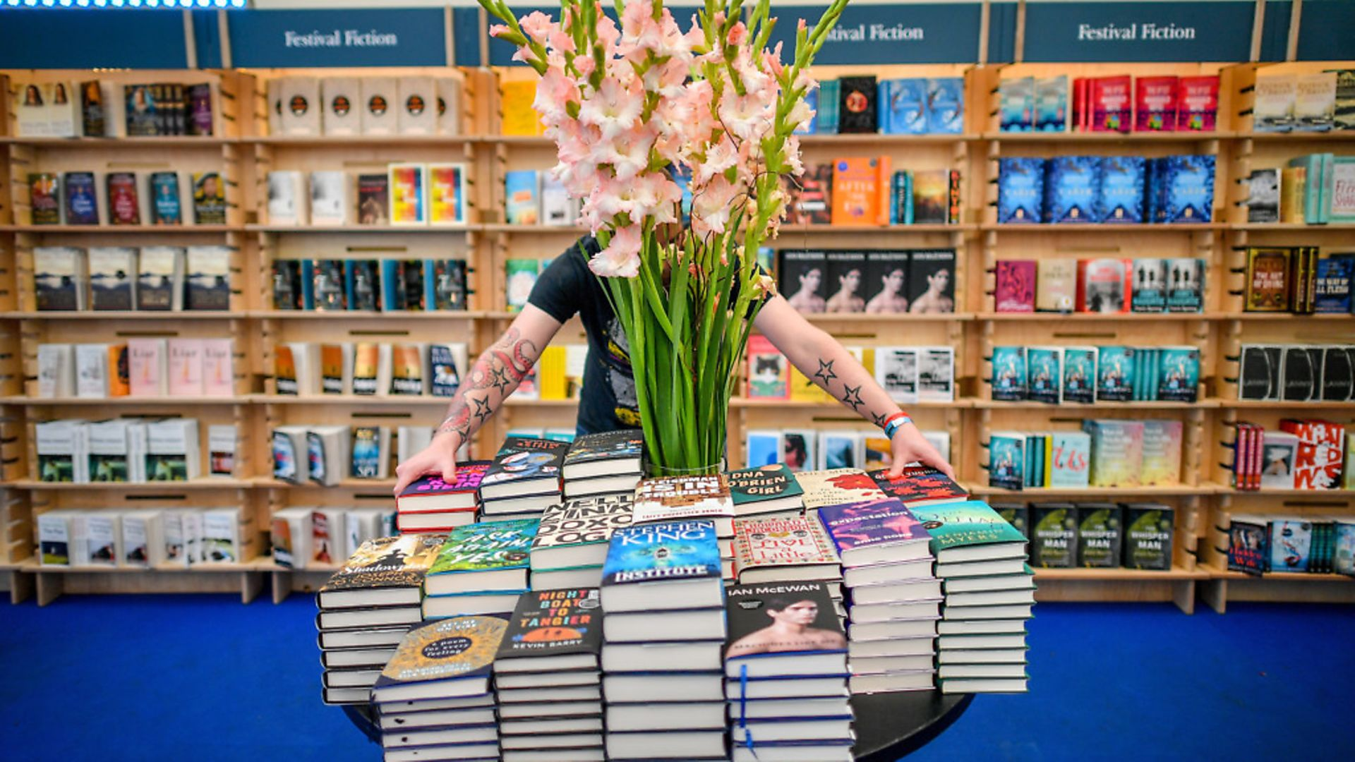 A worker organises and straightens books in a bookstore. Photograph: Ben Birchall/PA. - Credit: PA Wire/PA Images