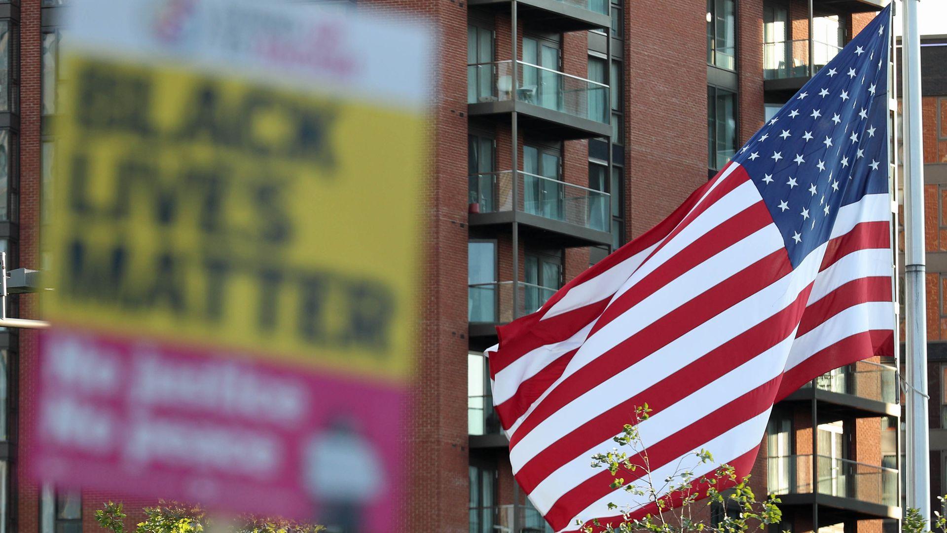 Black Lives Matter placard alongside the American flag - Credit: PA