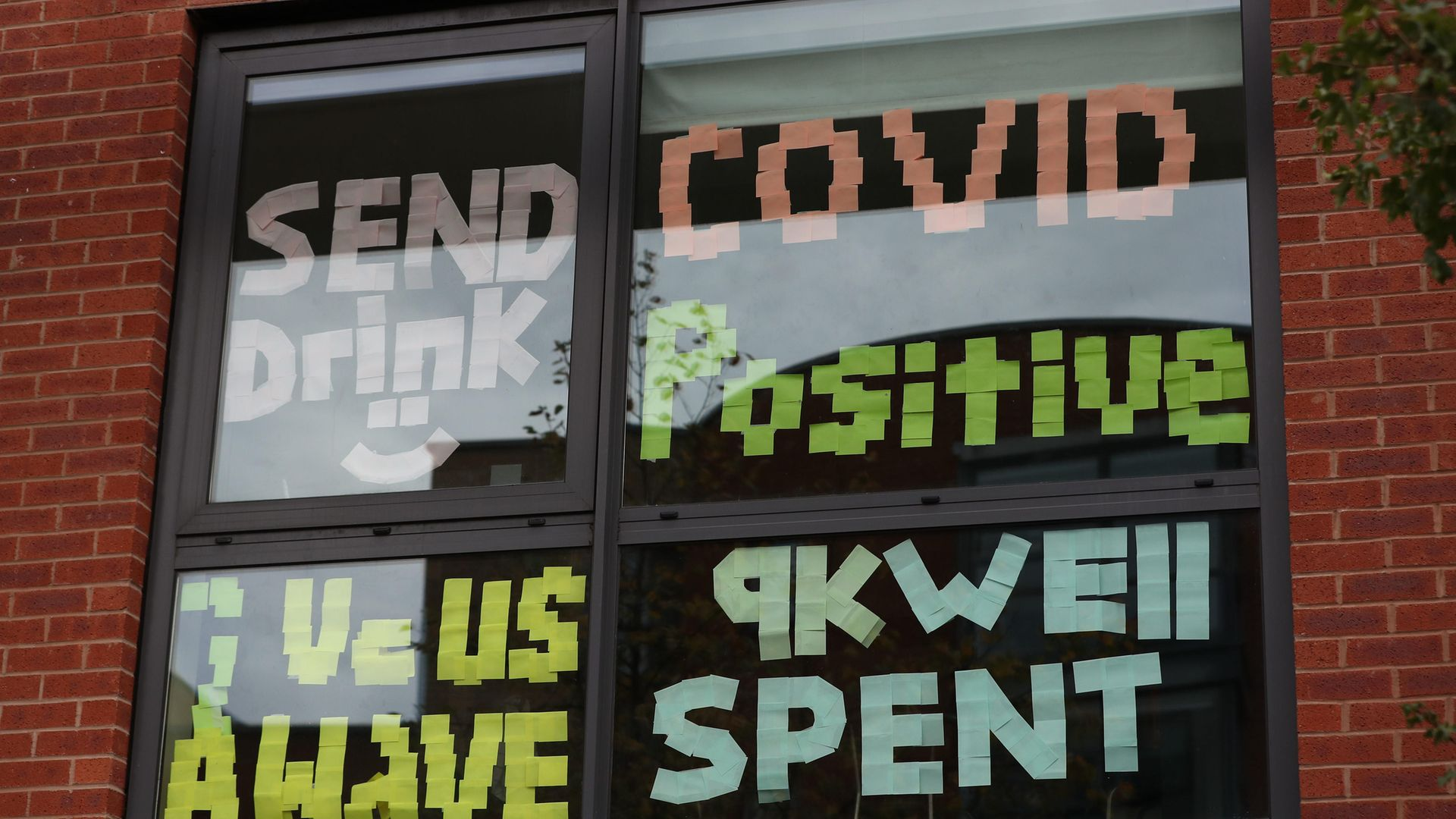 Signs on a window at a university as students self-isolate - Credit: PA