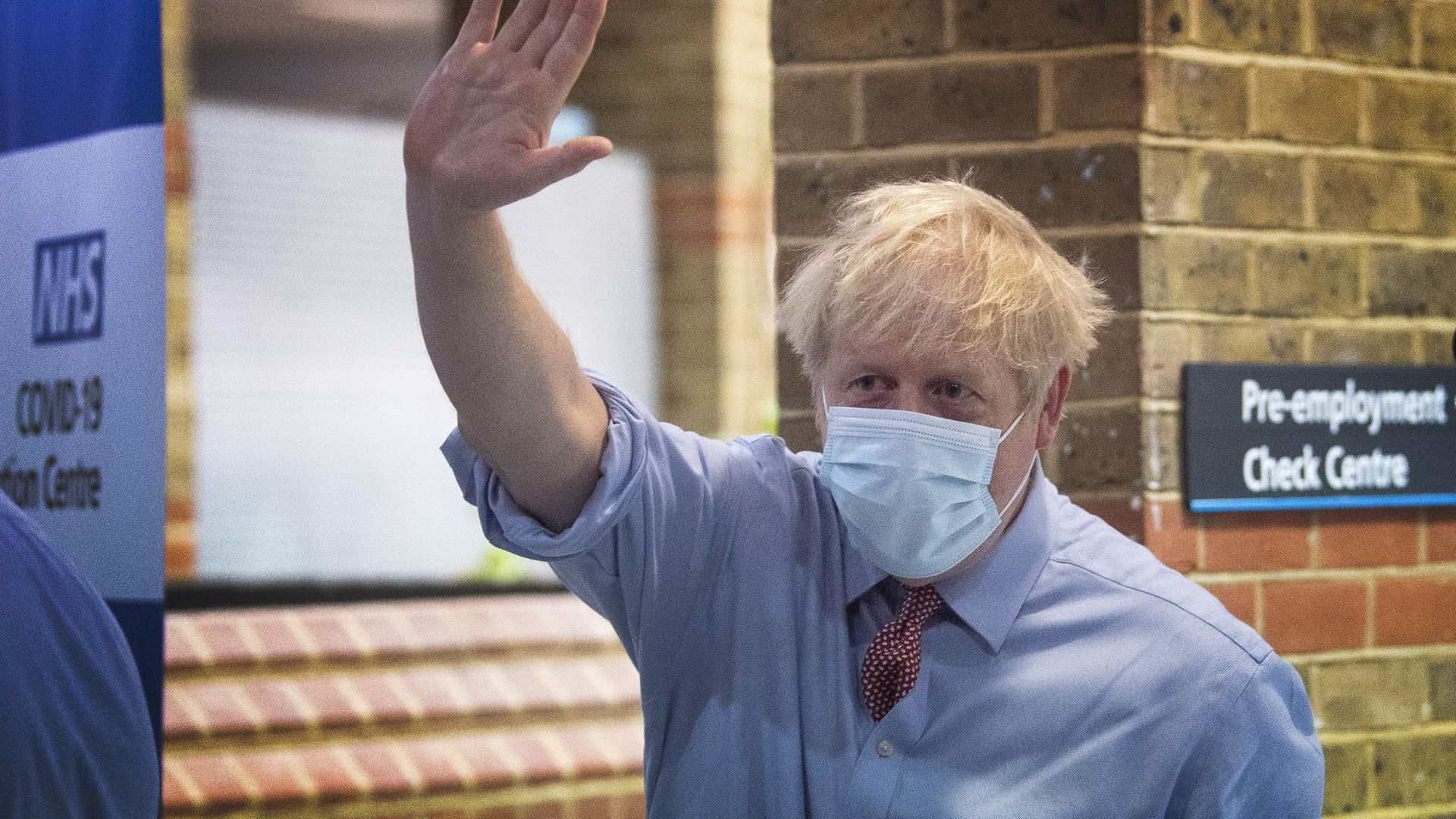 Prime minister Boris Johnson waves as he leaves Guy's Hospital in London, after watching a patient receive a Covid-19 vaccination jab on the first day of the largest immunisation programme in the UK's history - Credit: PA