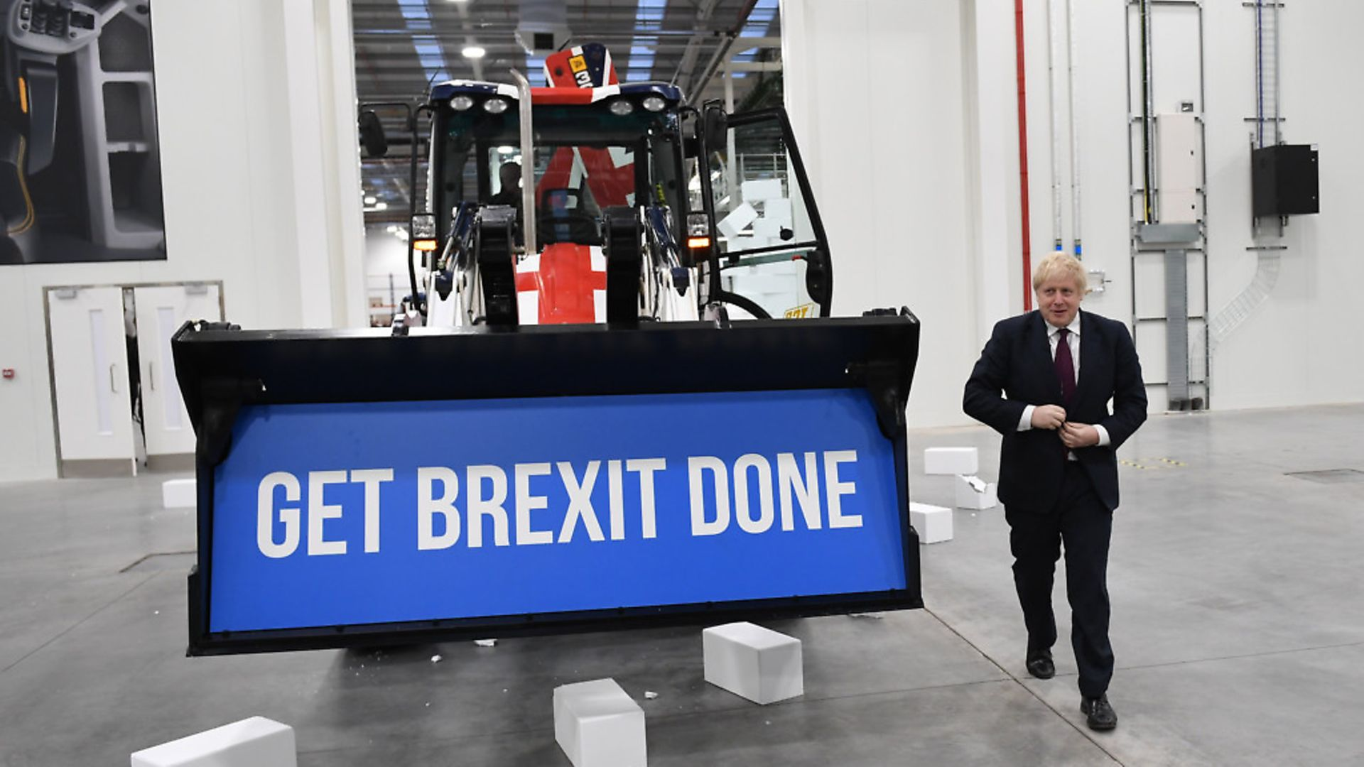 """Prime Minister Boris Johnson walks away after driving a union flag-themed JCB, with the words """"Get Brexit Done"""" inside the digger bucket. Photograph: Stefan Rousseau/PA. - Credit: PA Wire/PA Images"""