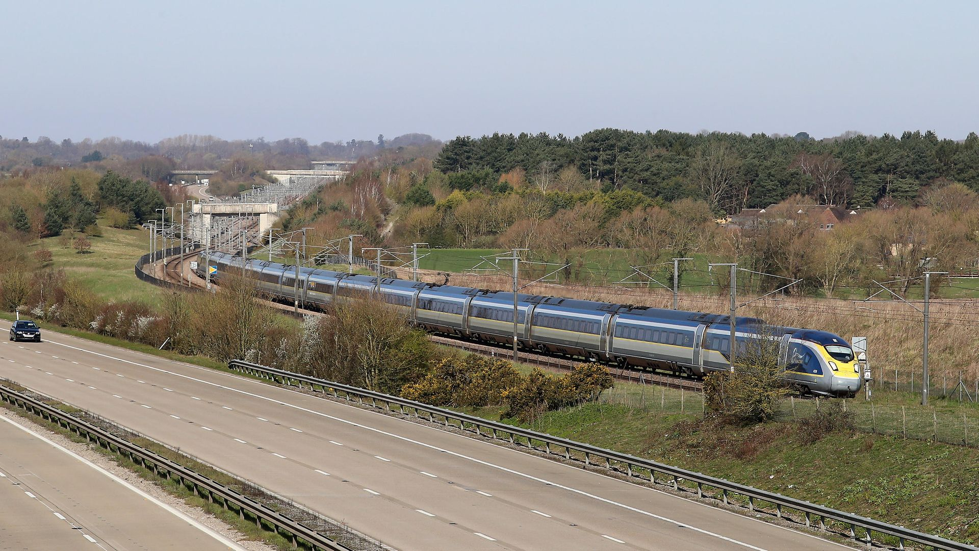 A Eurostar train passes a quiet M20 near Ashford in Kent - Credit: PA