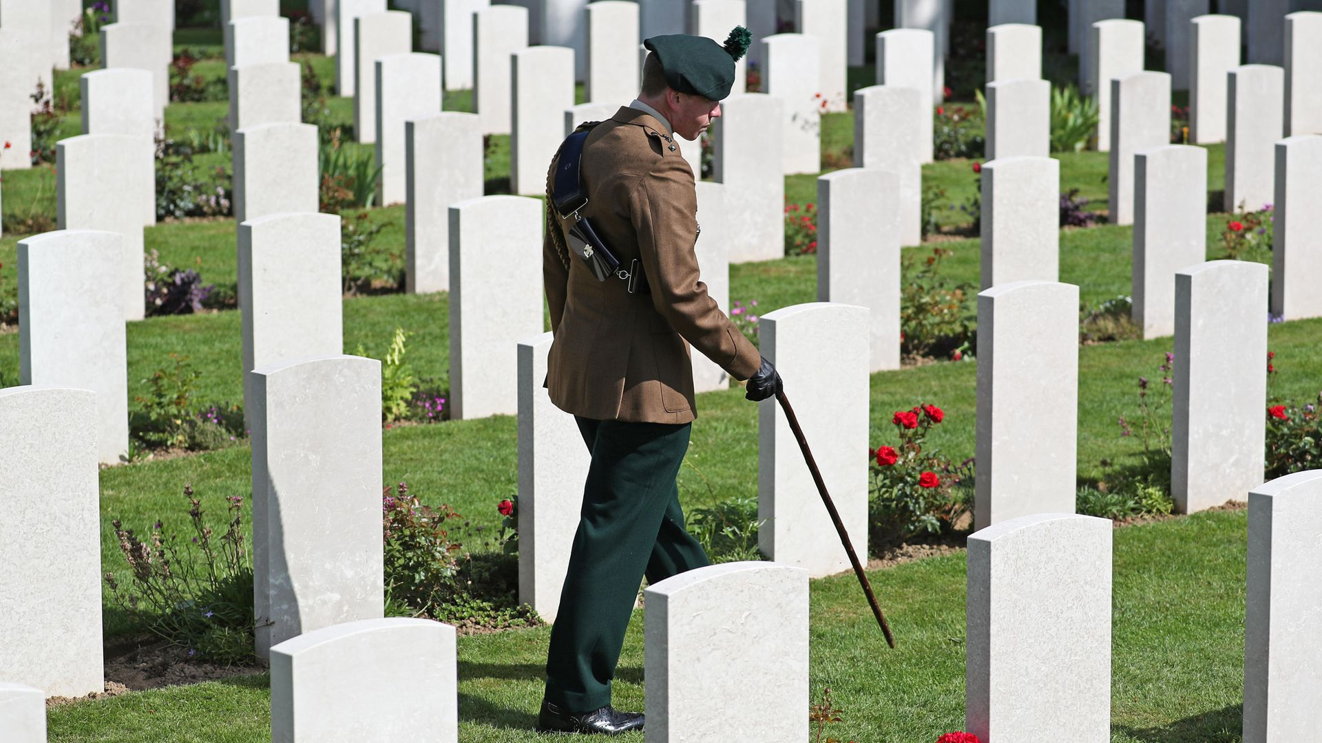 A man in uniform walks past the graves of fallen soldiers during the Royal British Legion's Service of Remembrance, at the Commonwealth War Graves Commission Cemetery, in Bayeux, France, as part of commemorations for the 75th anniversary of the D-Day landings. - Credit: PA