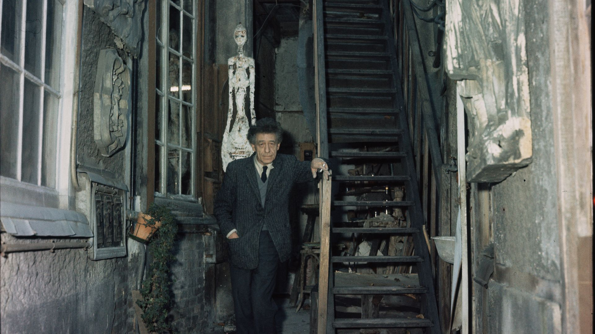 Alberto Giacometti stands in the stairwell to his house, where the walls are decorated with his sculptures, 1958 - Credit: Corbis/VCG via Getty Images
