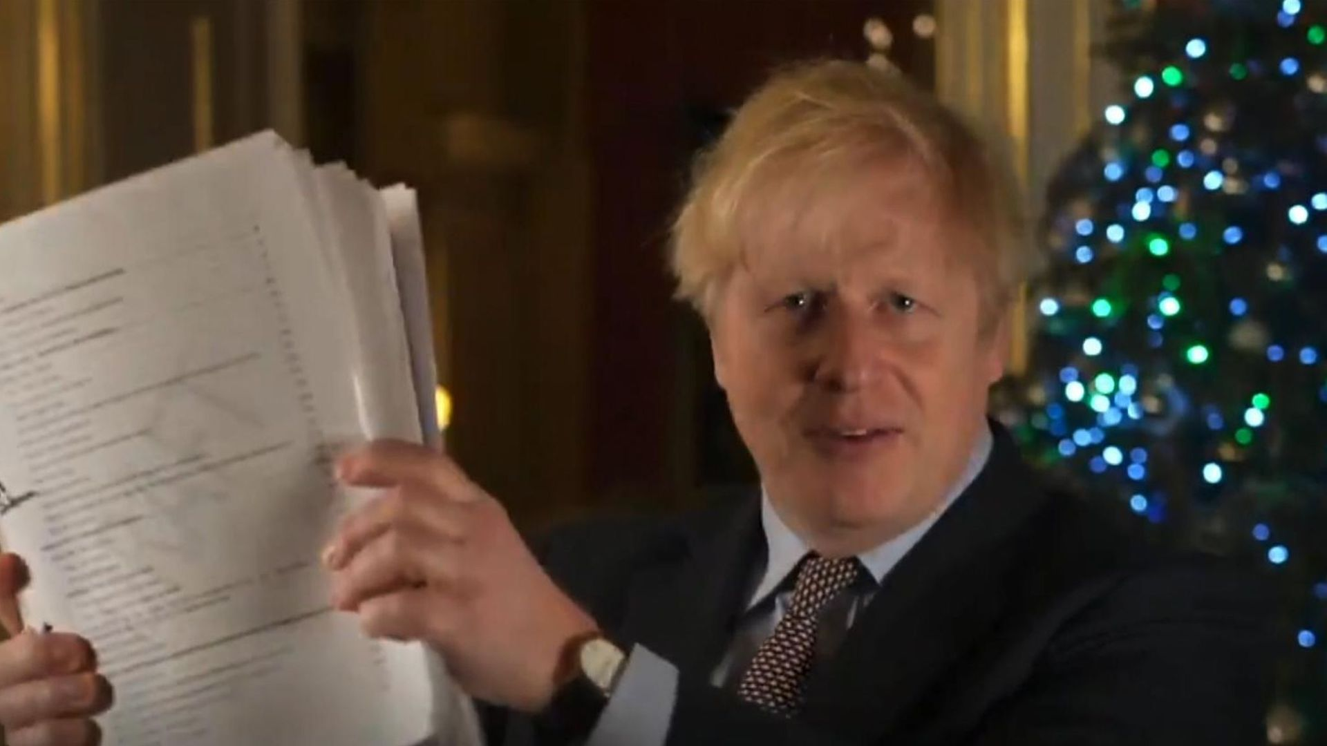 Boris Johnson holds up his Brexit agreement in a Christmas message - Credit: Twitter