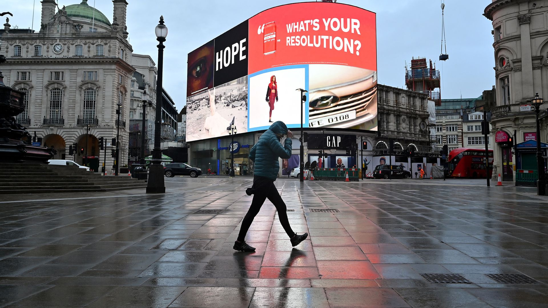 A pedestrian shelters from the rain as they walk across an almost deserted Piccadilly Circus as Britain enters the latest lockdown - Credit: AFP via Getty Images