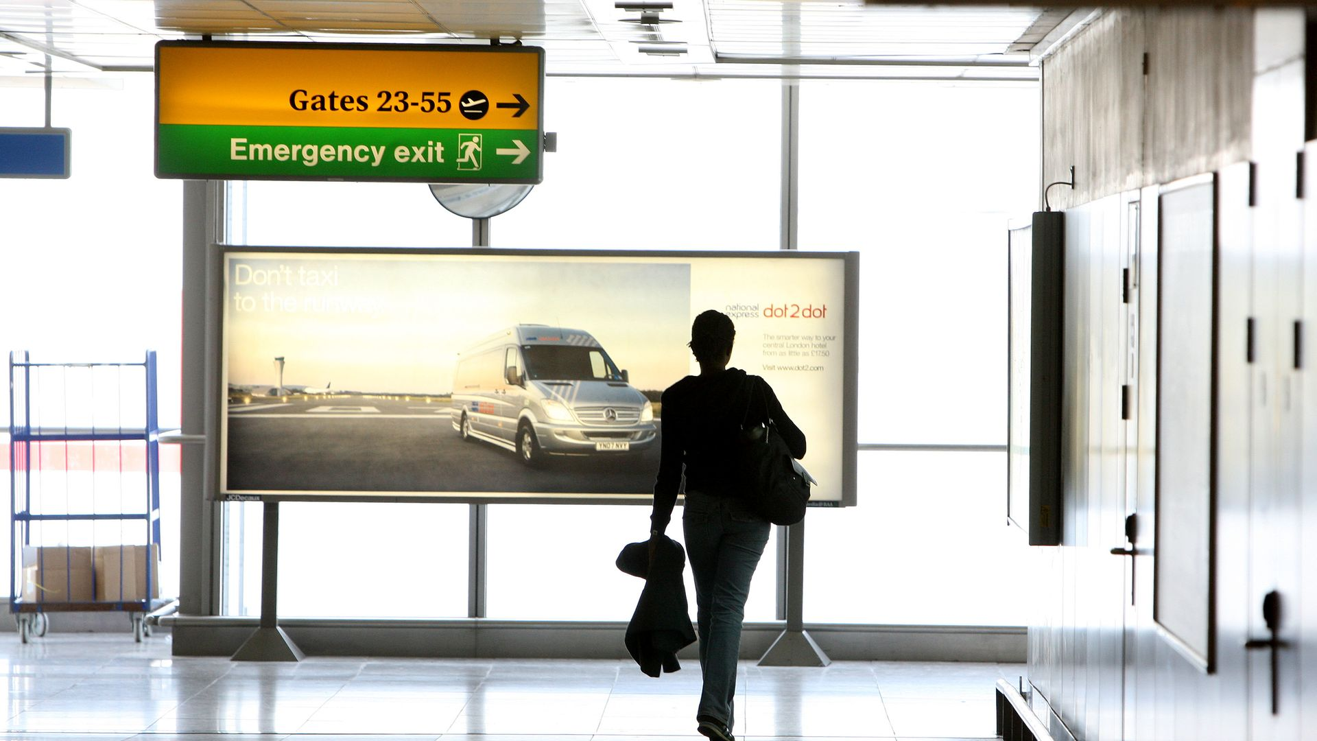 A picture of a passenger walking between departure gates in Terminal 3 at Heathrow Airport - Credit: PA