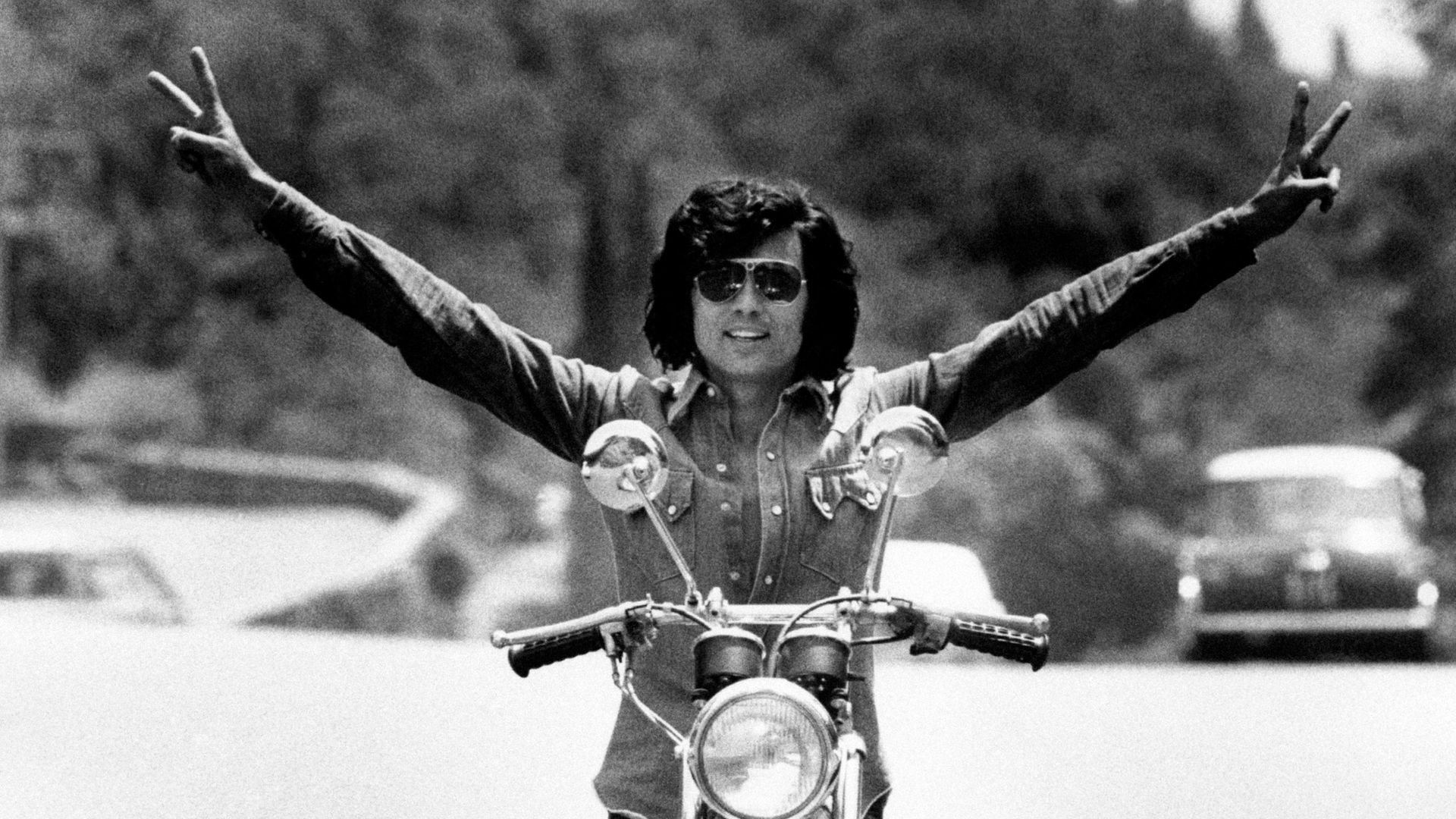 The Sammarinese singer Little Tony, born Antonio Ciacci, poses on a motorbike with open arms. - Credit: Mondadori via Getty Images