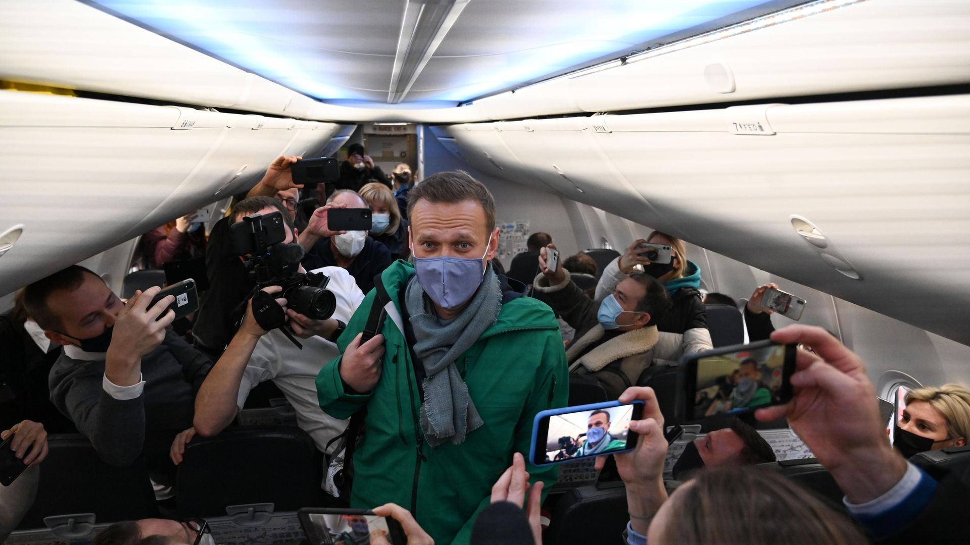 Russian opposition leader Alexei Navalny walks to take his seat on the aircraft taking him from Berlin to Moscow - Credit: AFP via Getty Images