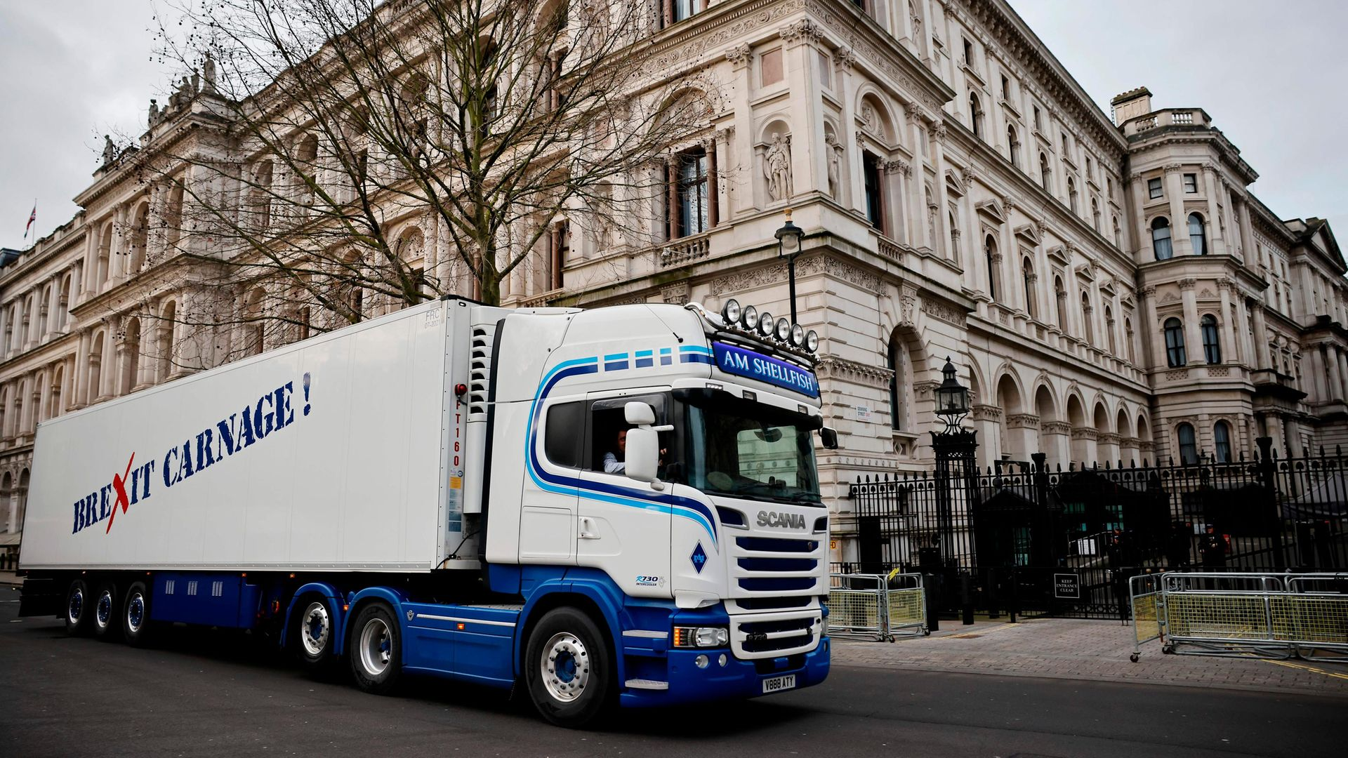 """A truck drives past Downing Street with a message that reads """"Brexit carnage!"""" in a protest action by Scottish fishermen against post-Brexit red tape and coronavirus restrictions, which they say could threaten the future of the industry, in London on January 18, 2021 - Credit: AFP via Getty Images"""