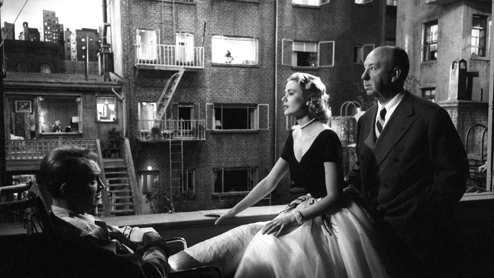 Grace Kelly and Jimmy Stewart with Alfred Hitchcock on the set of Rear Window - Credit: Getty Images